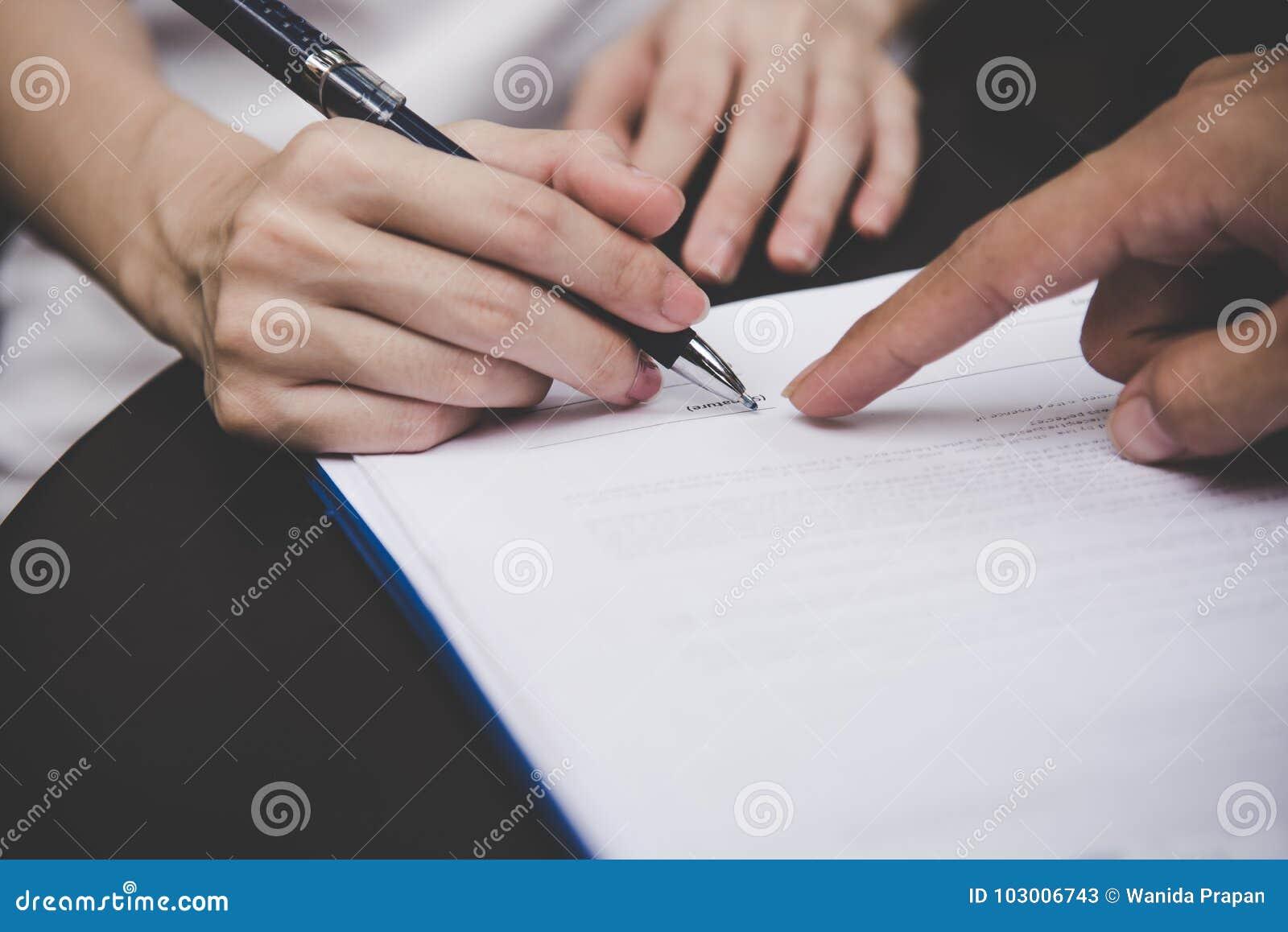 Vrouwenhand die een contract voor de bouw van huis met de architectenmens ondertekenen