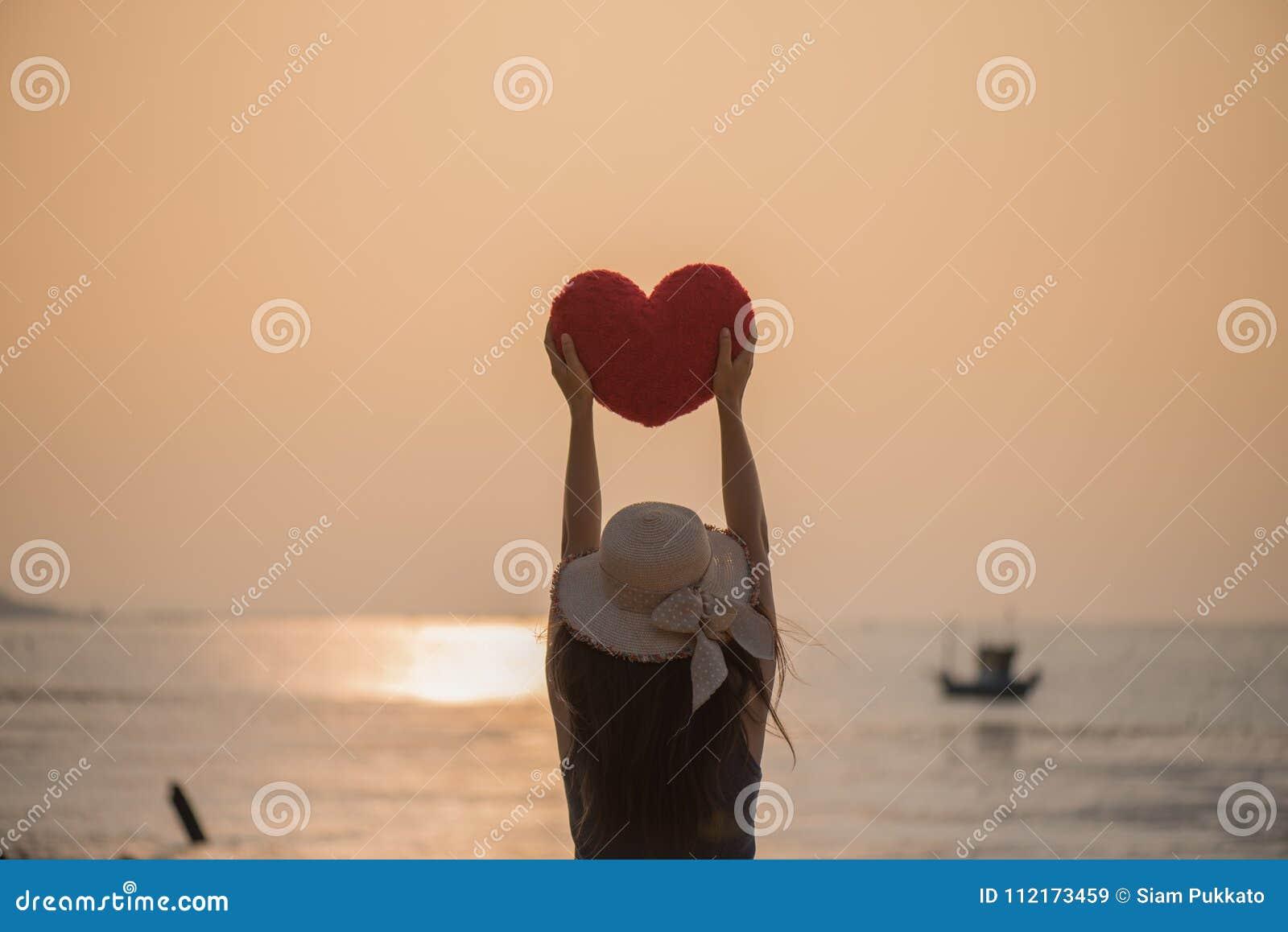 Vrouwenhand die een rood die hoofdkussen in hart houden op het strand wordt gevormd