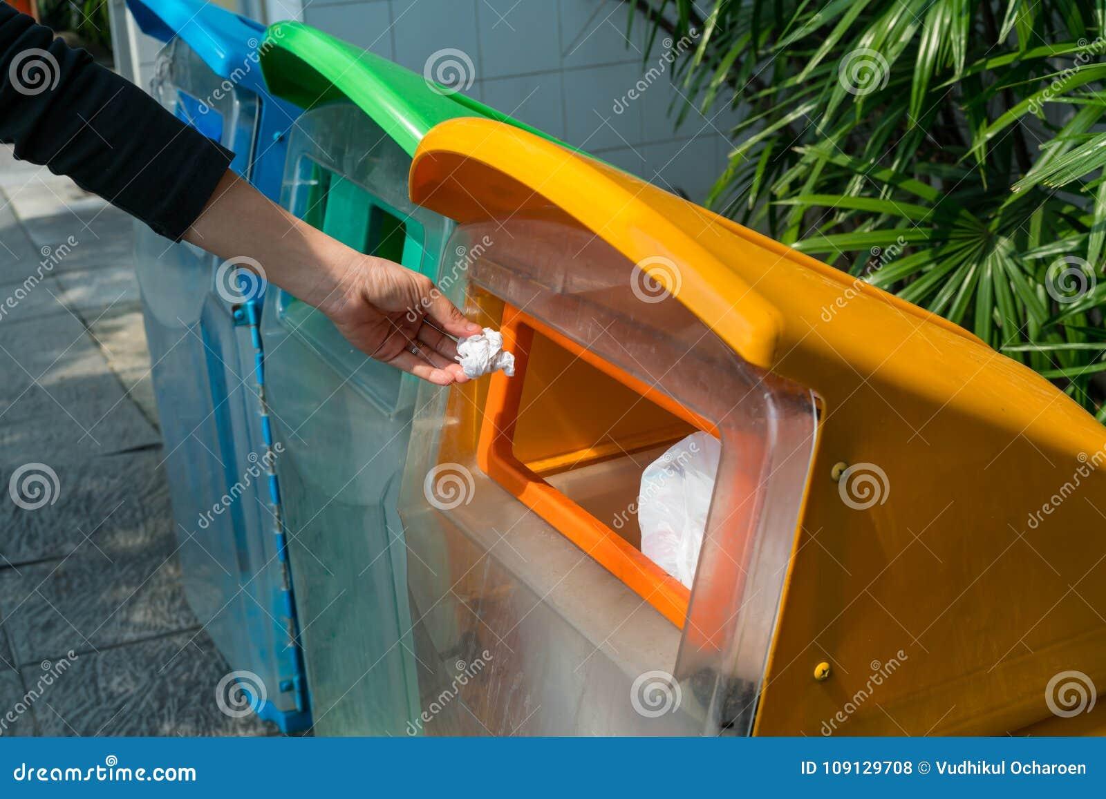 Vrouwenhand die gebruikt document in gerecycleerde bak zetten bij parkeerterrein D