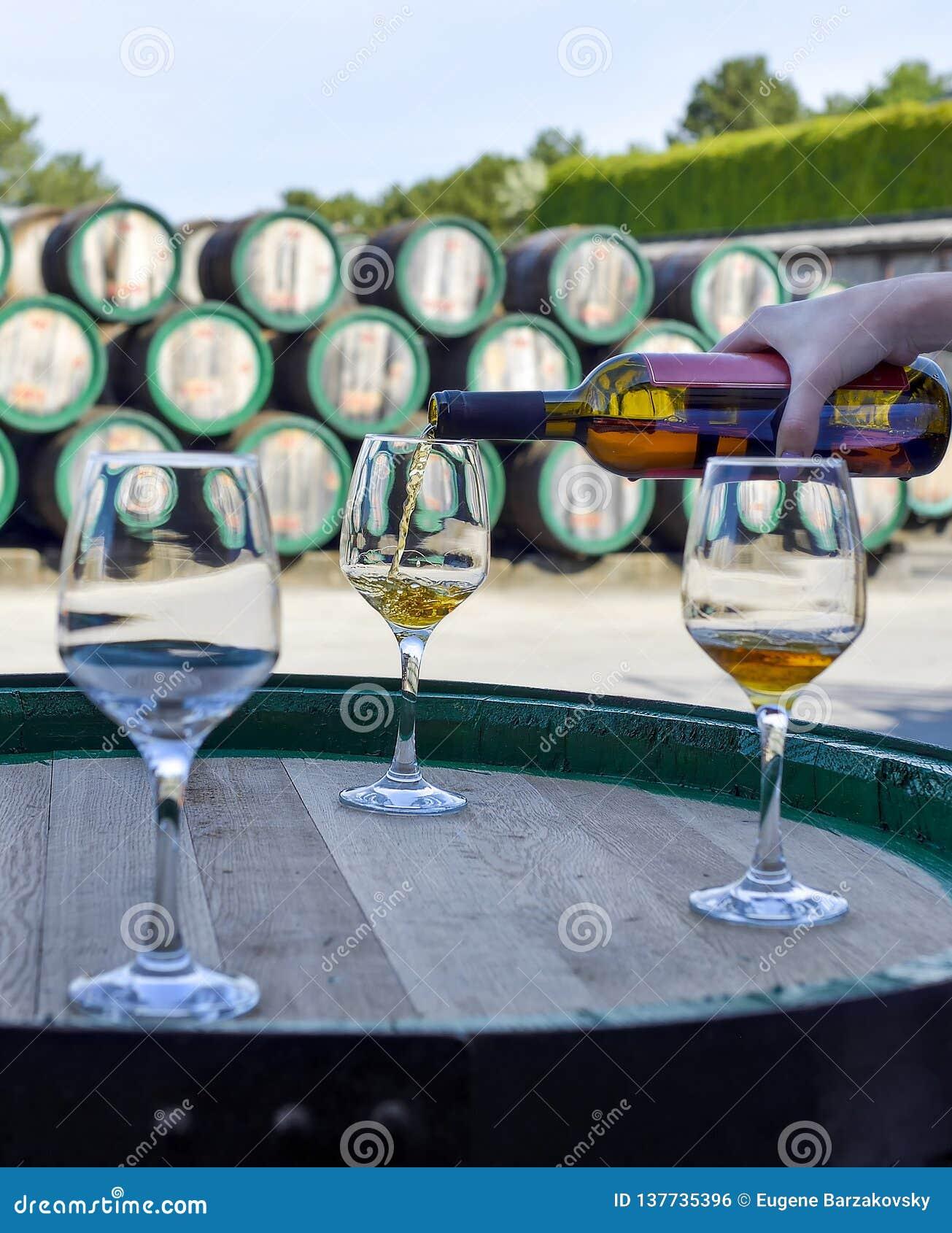Vrouwenhand die gouden wijn van de fles gieten in glazen