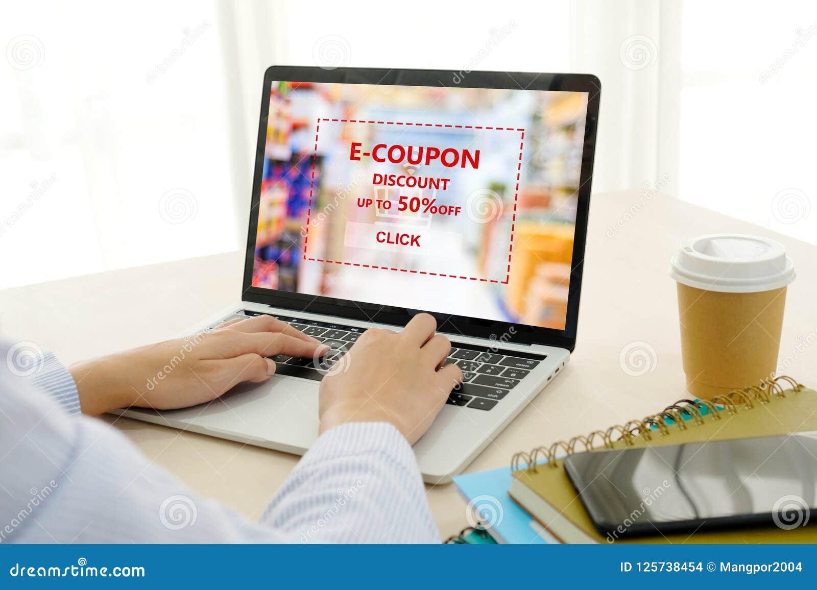 Vrouwenhand die laptop computer met kruidenierswinkel e-Coupon met behulp van, korting