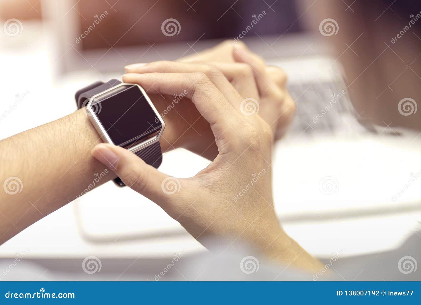 Vrouwenhand met slim horloge op pols, wearable horloge en laptop van de technologiecomputer voor mededeling, die tijd controleren
