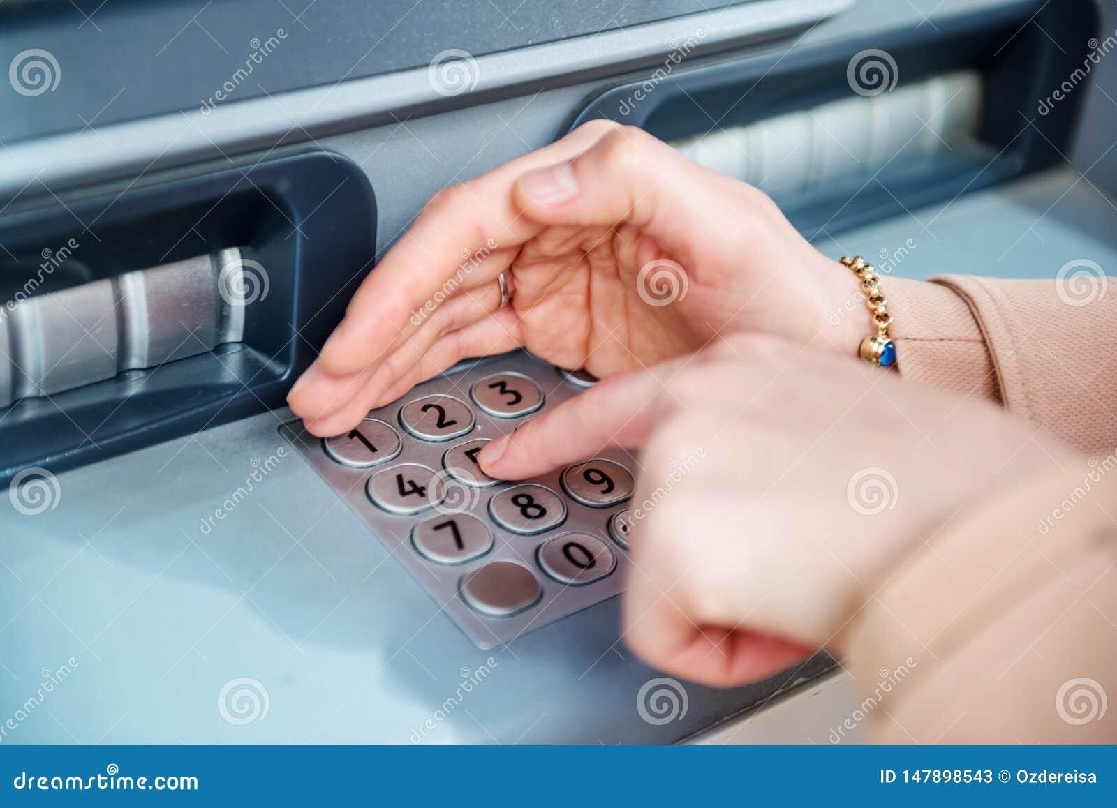 Vrouwenhand terwijl het gebruiken van ATM bij straat