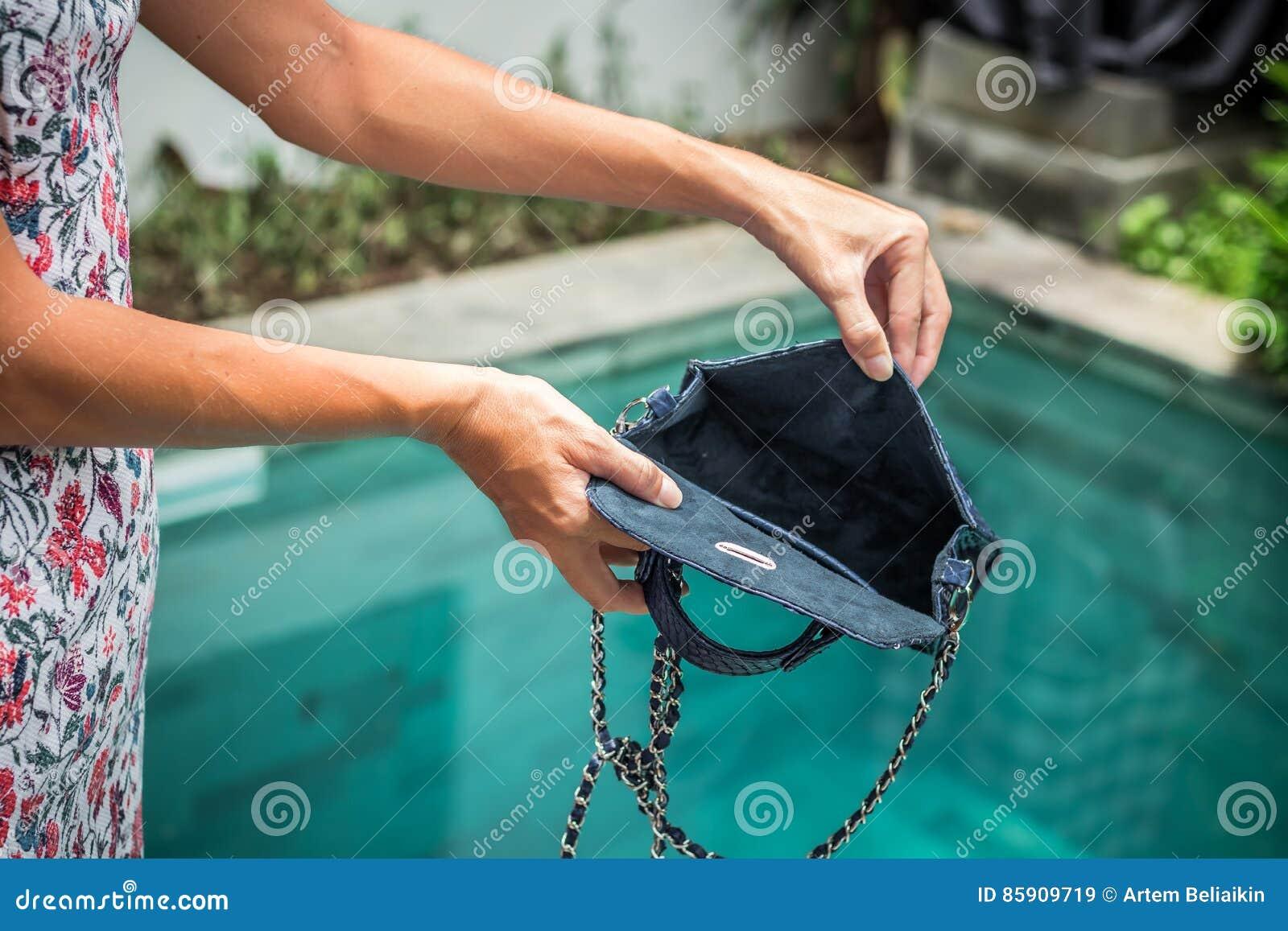 Vrouwenhanden die de lege handtas van de luxe snakeskin python op een zwembadachtergrond openen