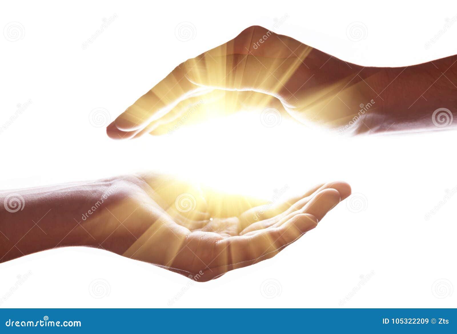 Vrouwenhanden die en helder, gloeiend, stralend, het glanzen licht beschermen bevatten Het uitzenden van zich stralen of stralen