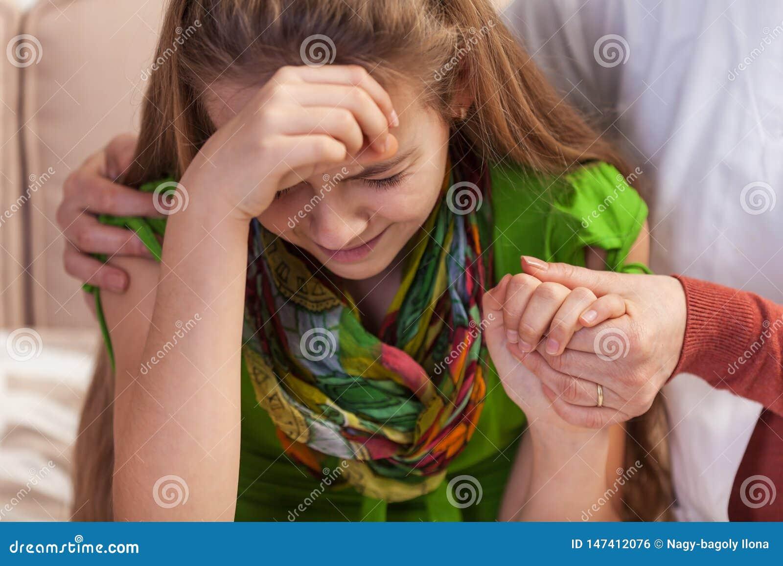 Vrouwenhanden die en schreeuwend jong meisje houden troosten Het tienerproblemenconcept, sluit omhoog