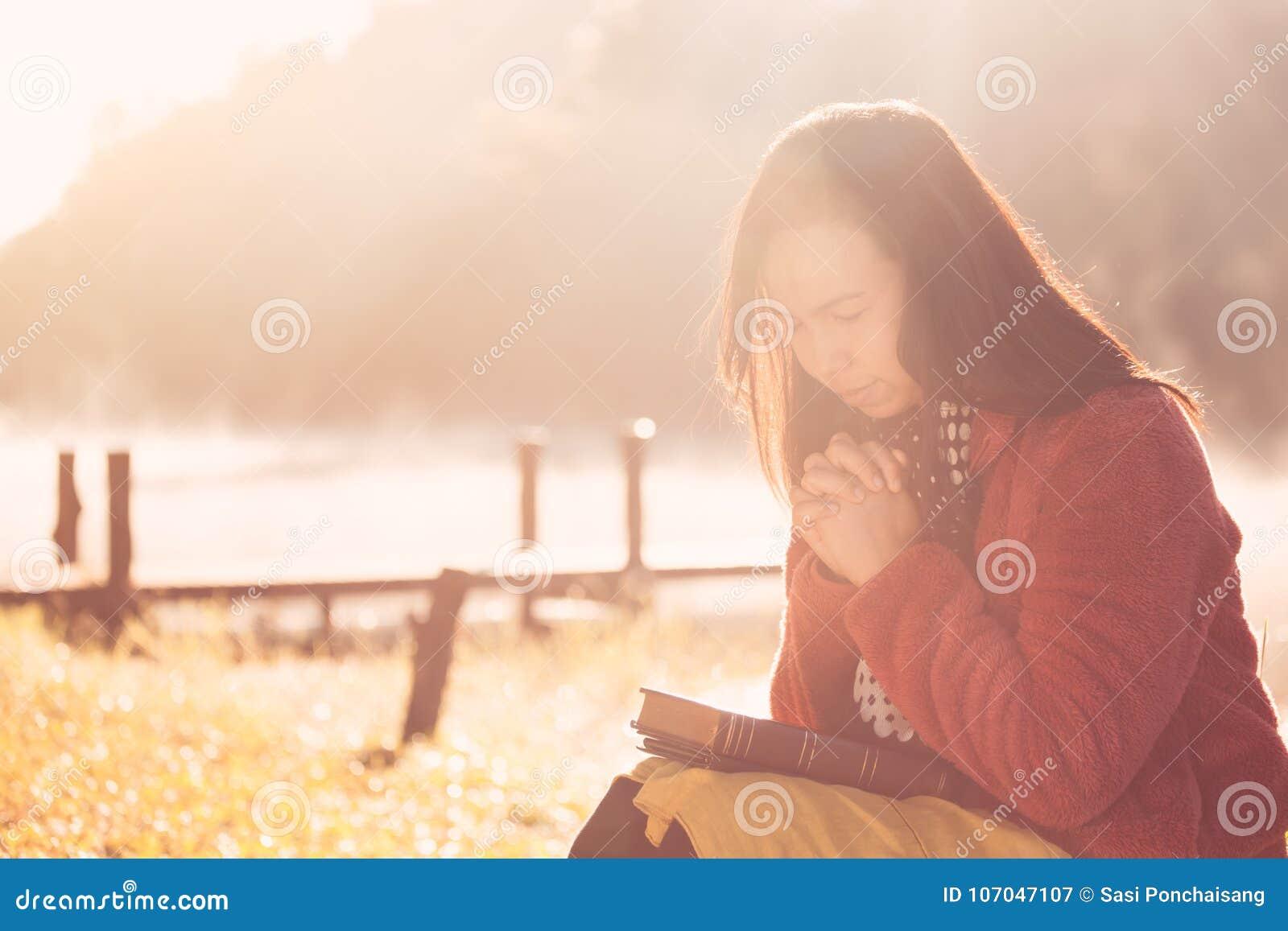 Vrouwenhanden in gebed op een Heilige Bijbel voor geloof worden gevouwen dat