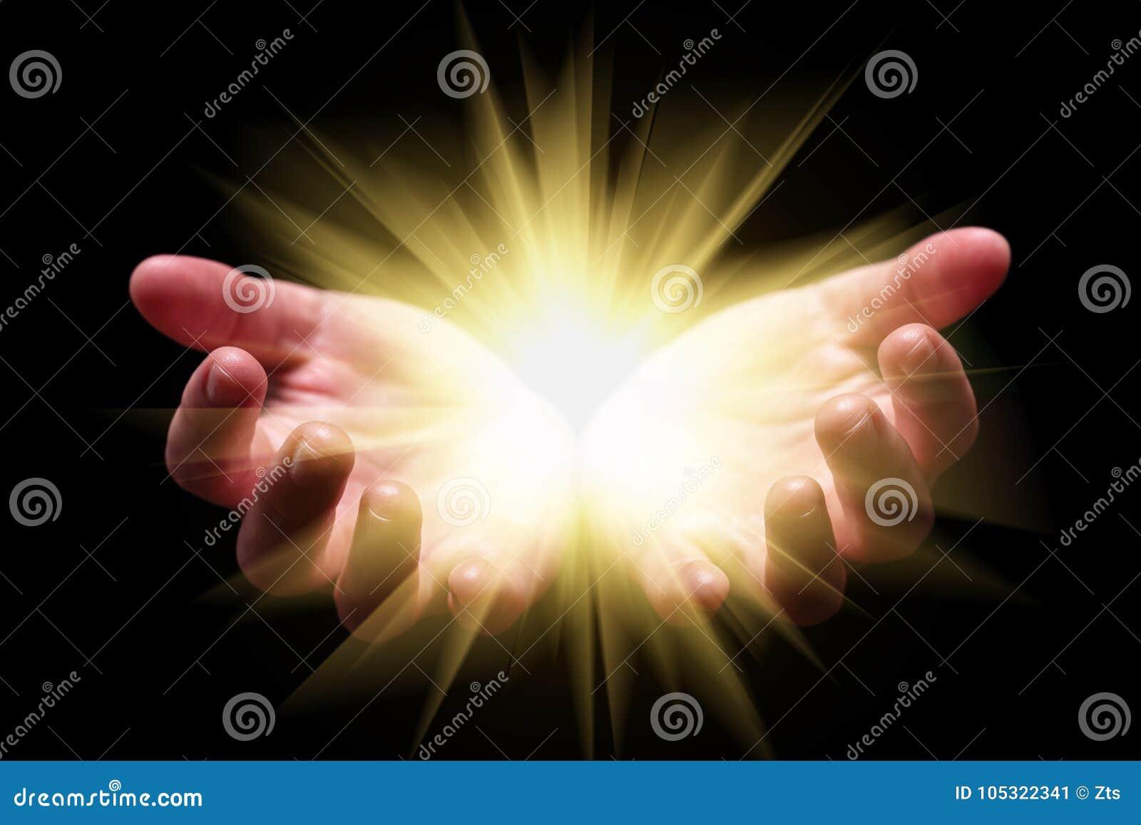 Vrouwenhanden tot een kom gevormde holding die, die of helder, gloeiend, stralend, het glanzen licht tonen afkomstig zijn