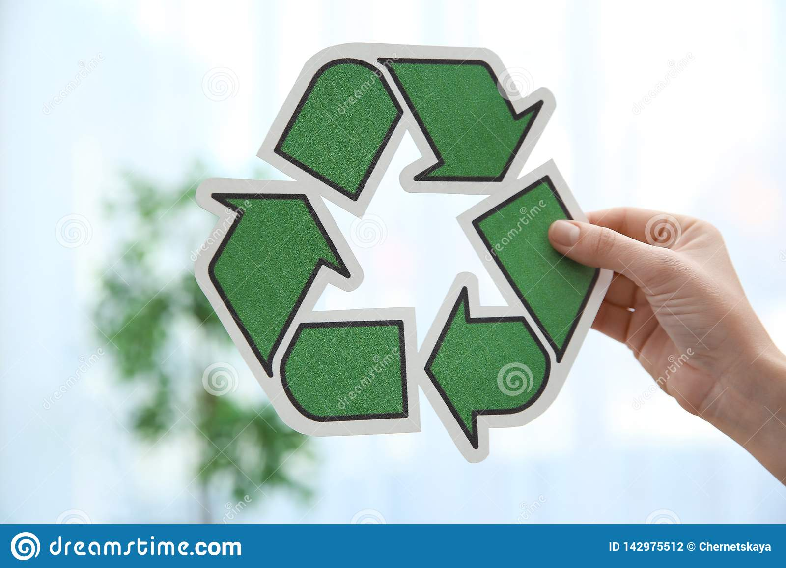 Vrouwenholding recyclingssymbool op vage achtergrond