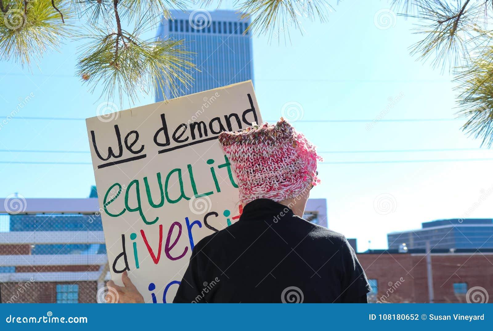 Vrouwenn roze pussy hoed met terug naar cameratribunes tegen stadshorizon met teken eisen wij Gelijkheidsdiversiteit bij Vrouwen