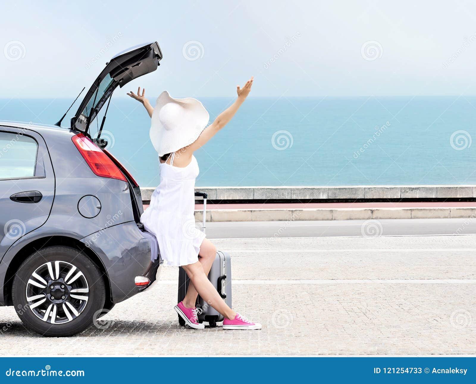 Vrouwenreiziger met opgeheven wapens op vijfdeursautoauto op strand