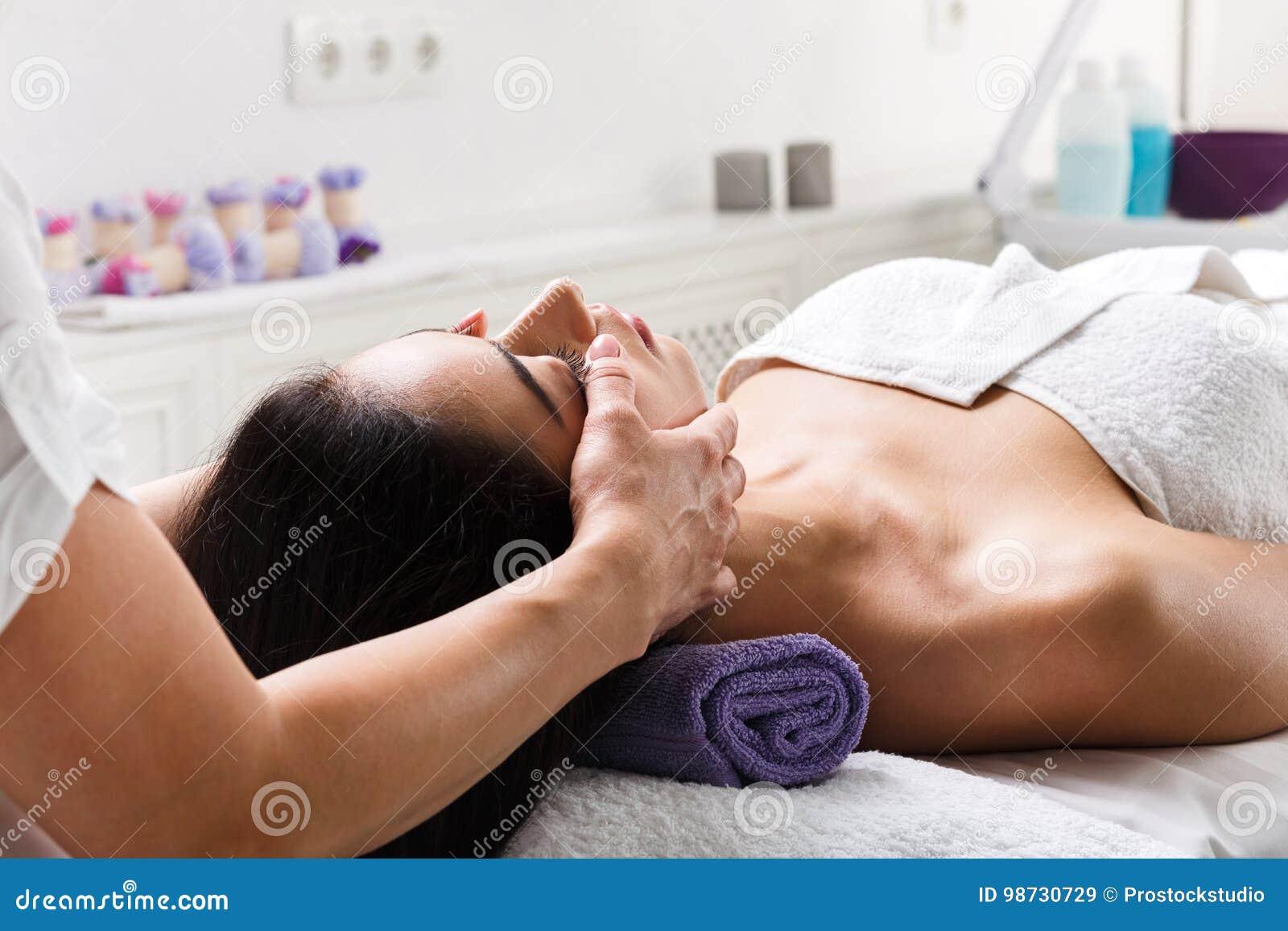 Vrouwenschoonheidsspecialist de arts maakt hoofdmassage in het centrum van kuuroordwellness