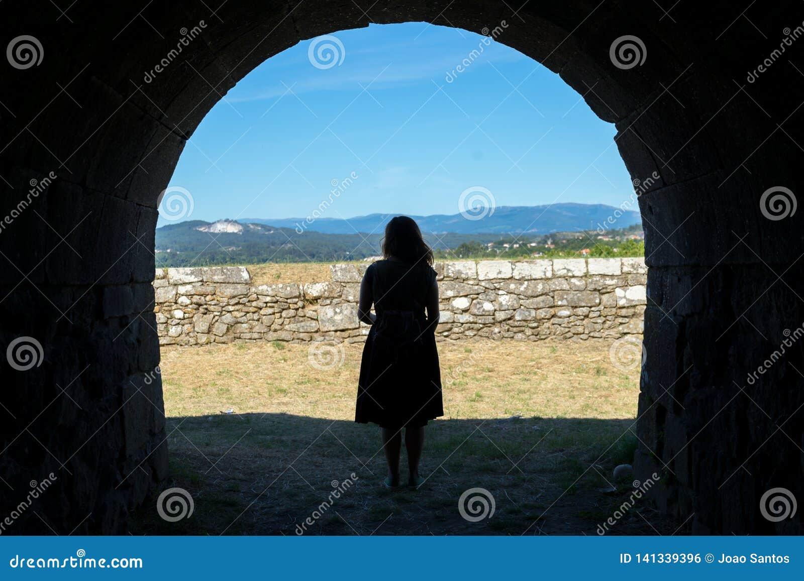 Vrouwensilhouet op een oude steentunnel