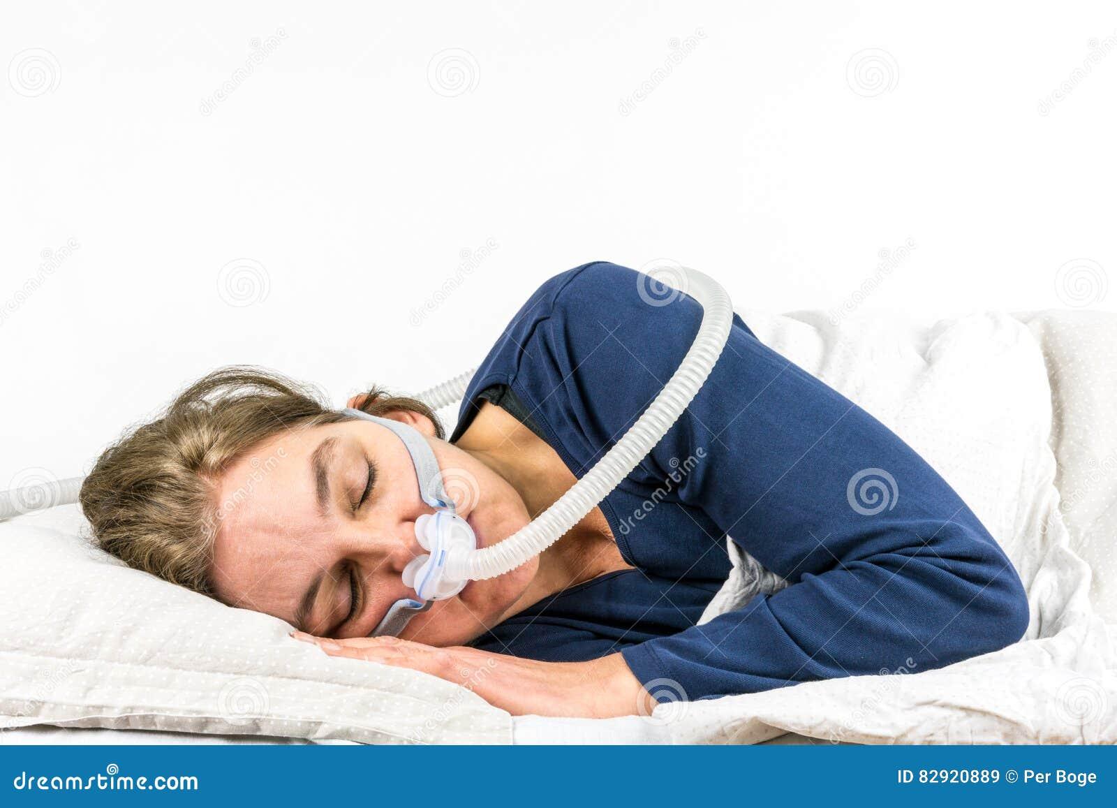 Vrouwenslaap aan haar kant met CPAP, de behandeling van slaapapnea