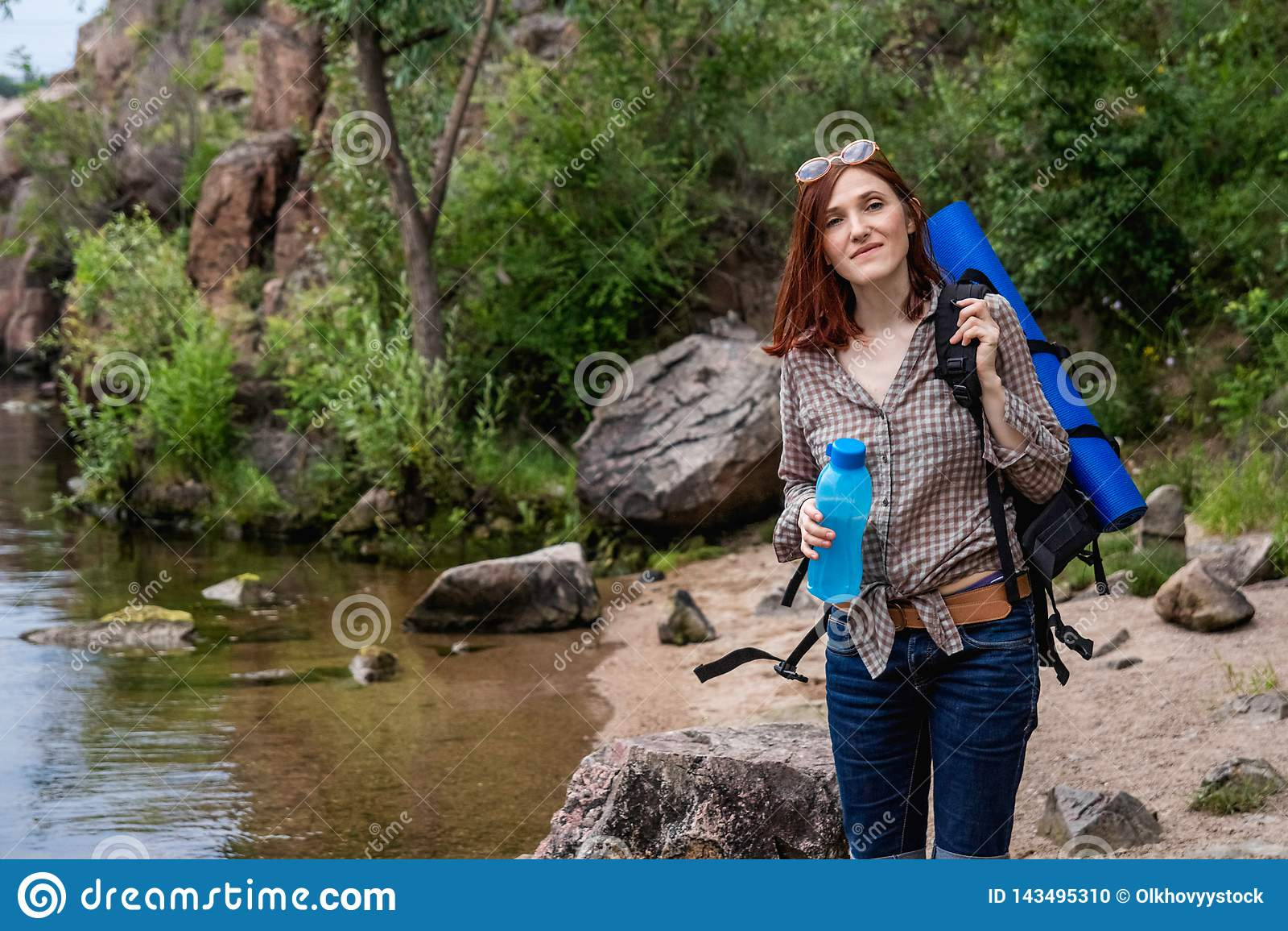 Vrouwentoerist met een rugzakgang in een stijging tegen een achtergrond van mooi berglandschap langs een bergrivier