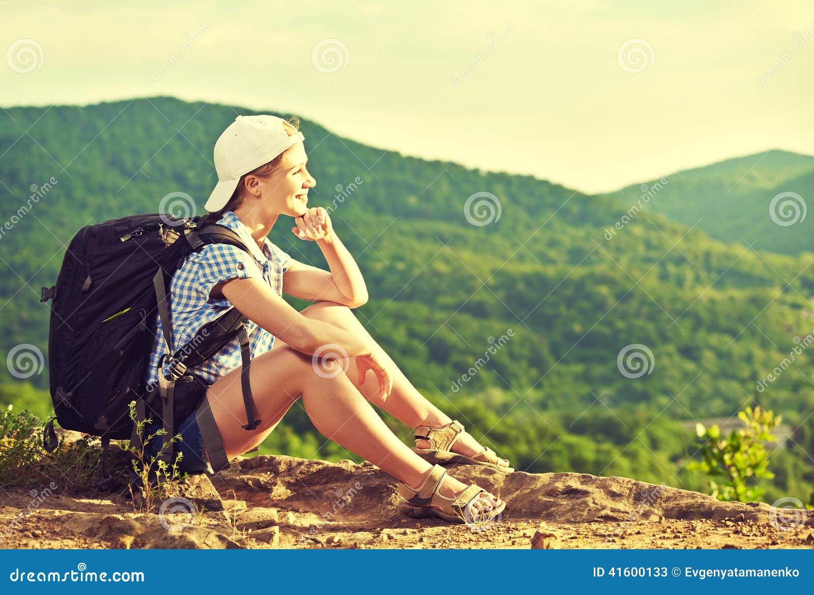 Vrouwentoerist met een rugzakzitting, die op een bergbovenkant rusten