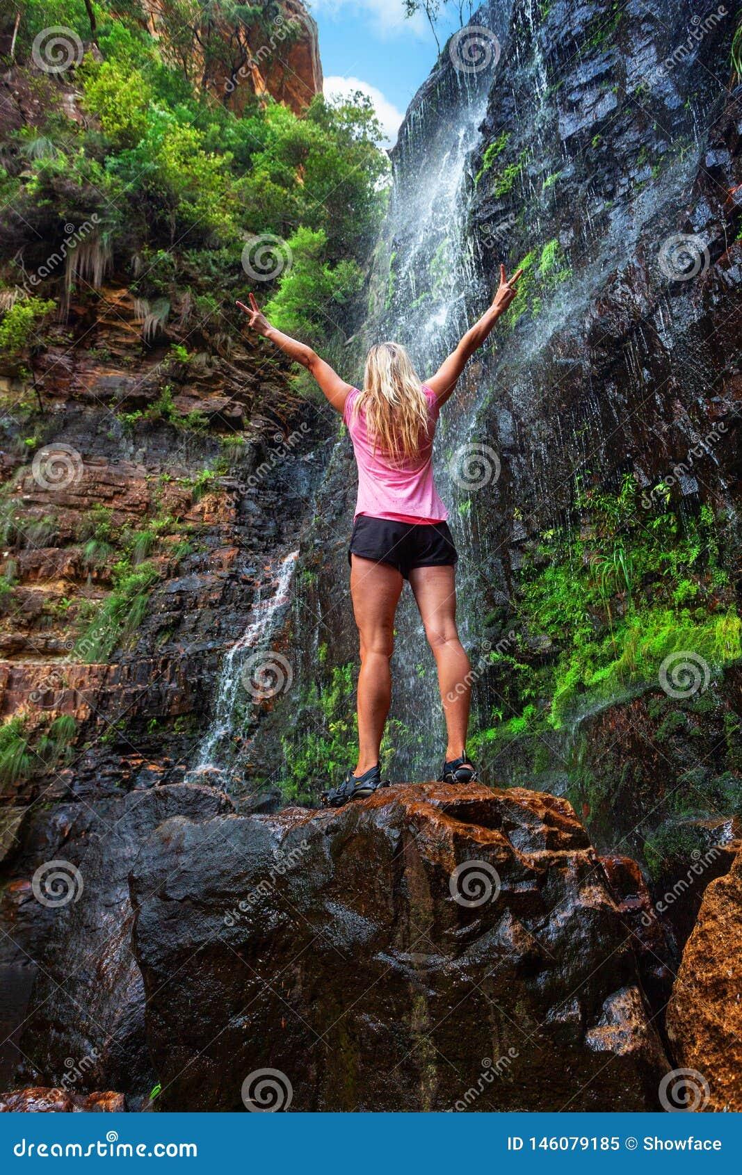 Vrouwentribunes op rots voor draperende waterval
