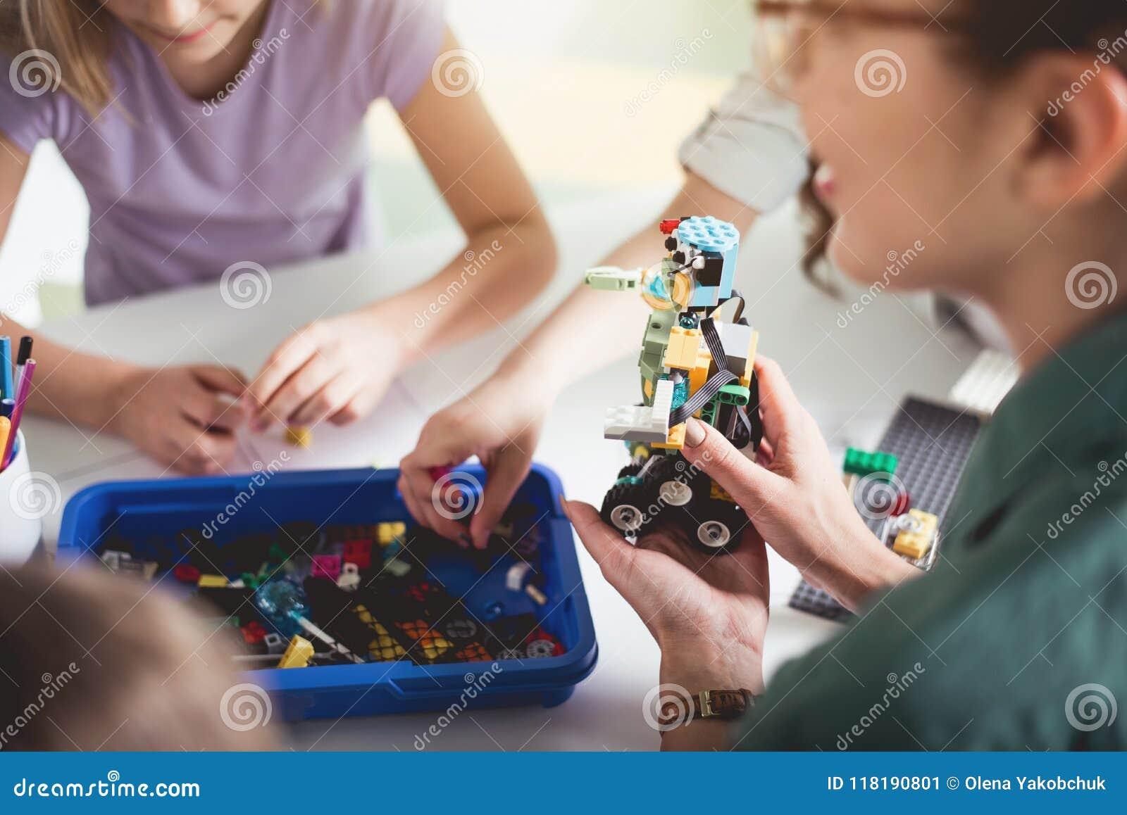 Vrouwenwapen die plastic stuk speelgoed houden