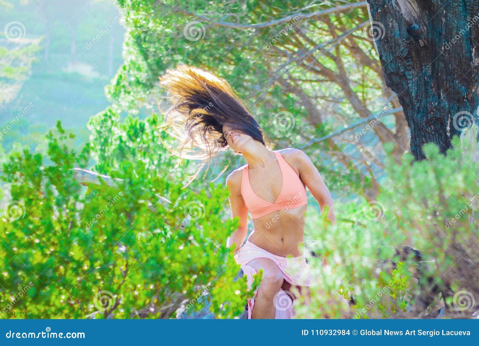 Vrouwenzitting in een bos die haar haar met bomen op de achtergrond flicking