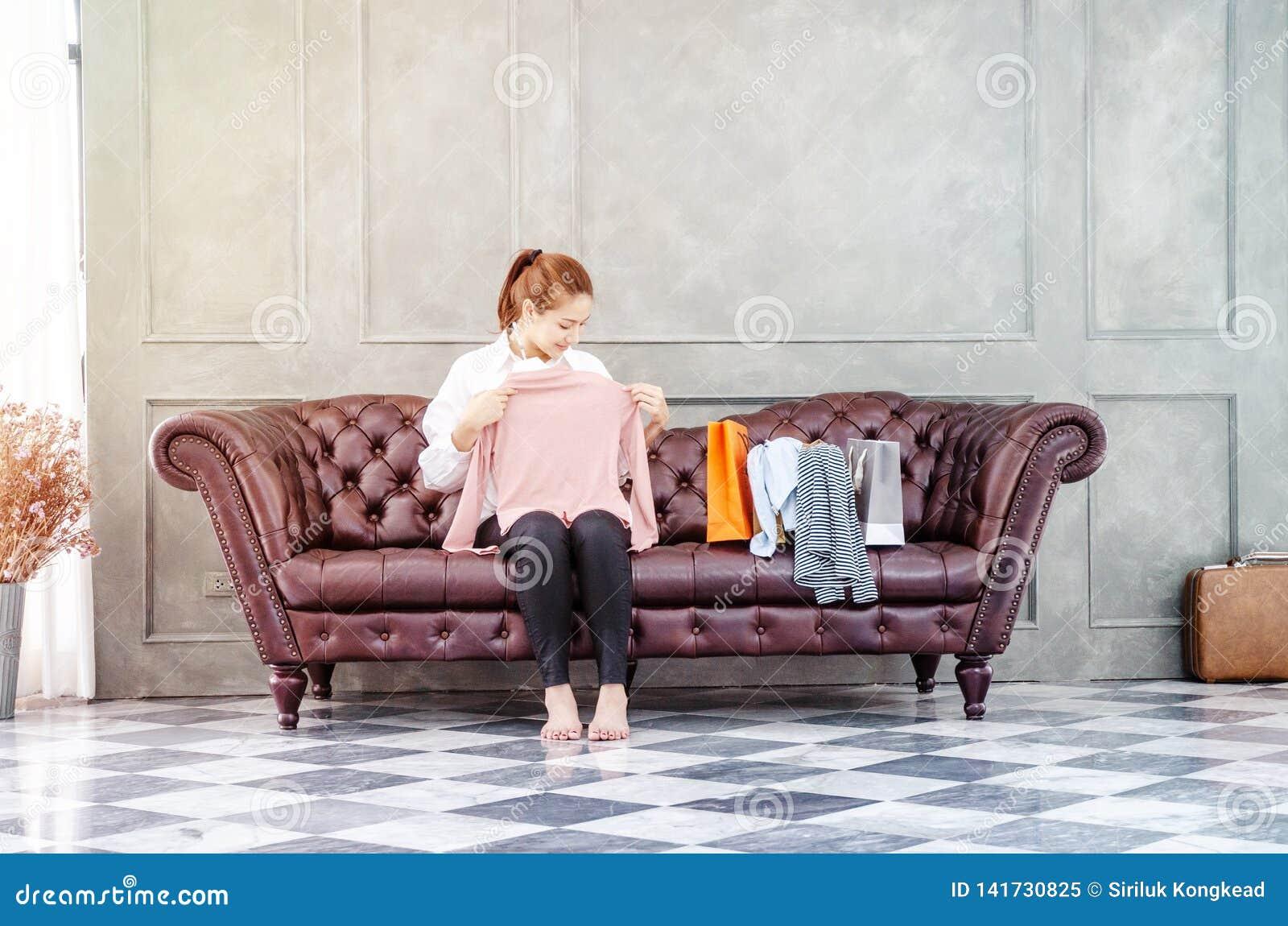 Vrouwenzitting op de bank houdt zij een roze overhemd en glimlacht
