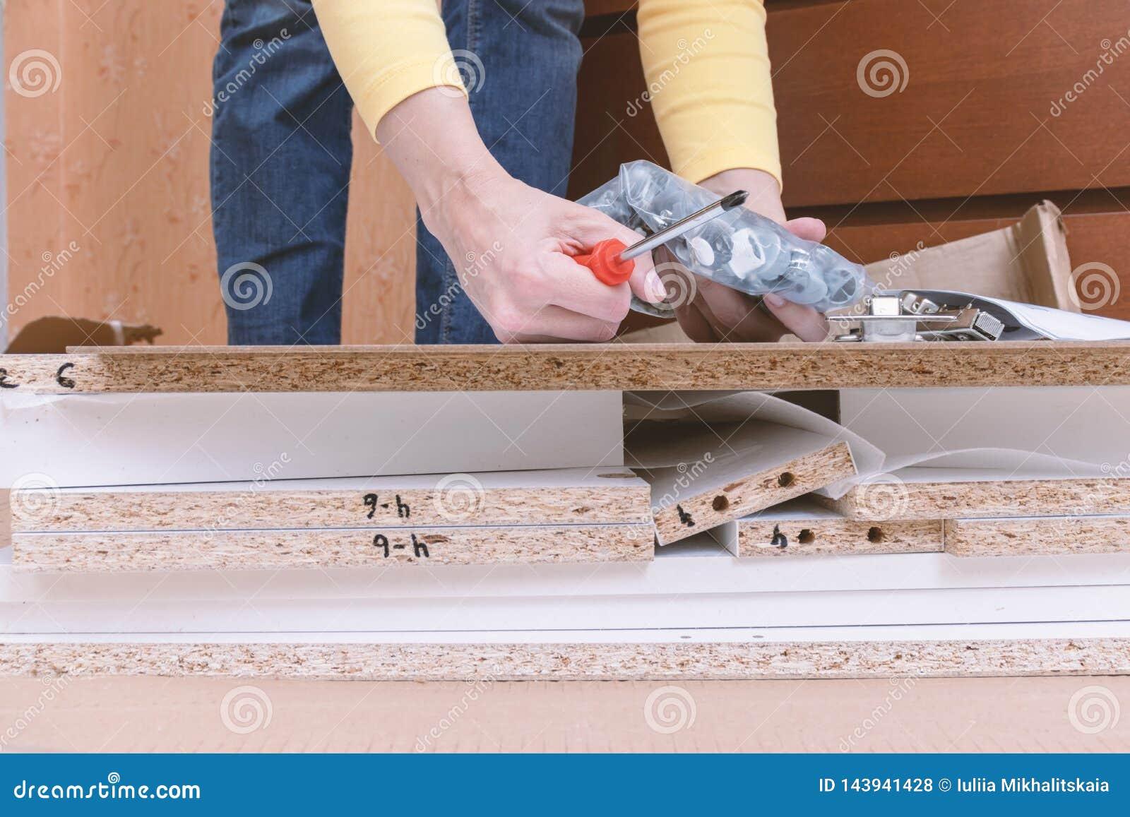 Vrouwenzitting op de vloer thuis en het assembleren meubilair die handhulpmiddelen met behulp van