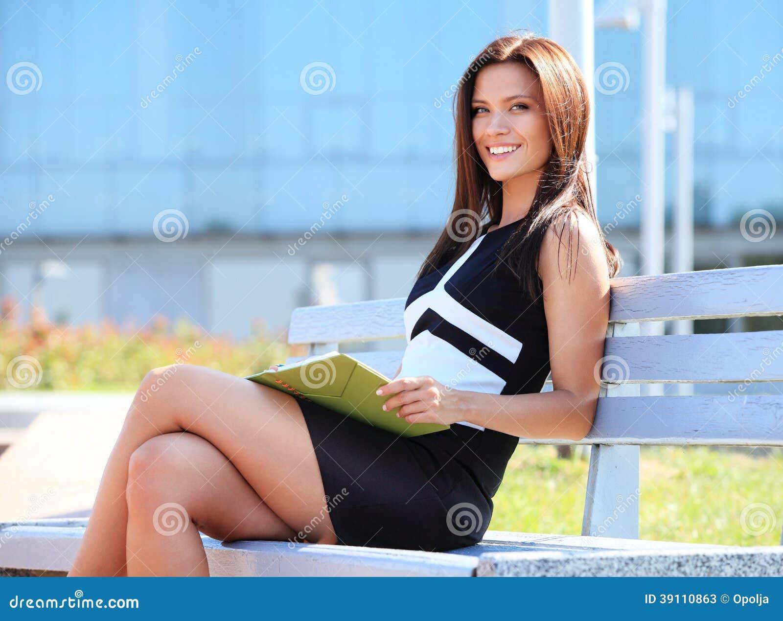Vrouwenzitting op een houten bank in een park
