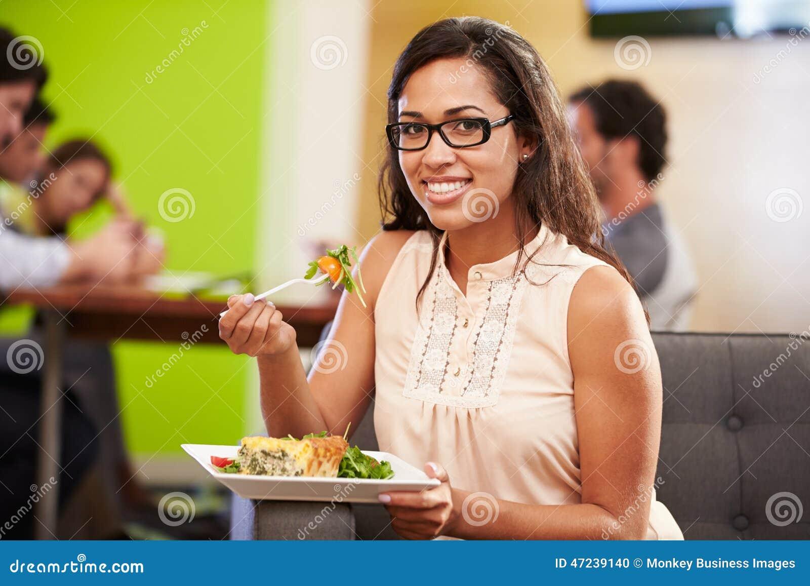 Vrouwenzitting op Sofa And Eating Lunch In-Ontwerpstudio