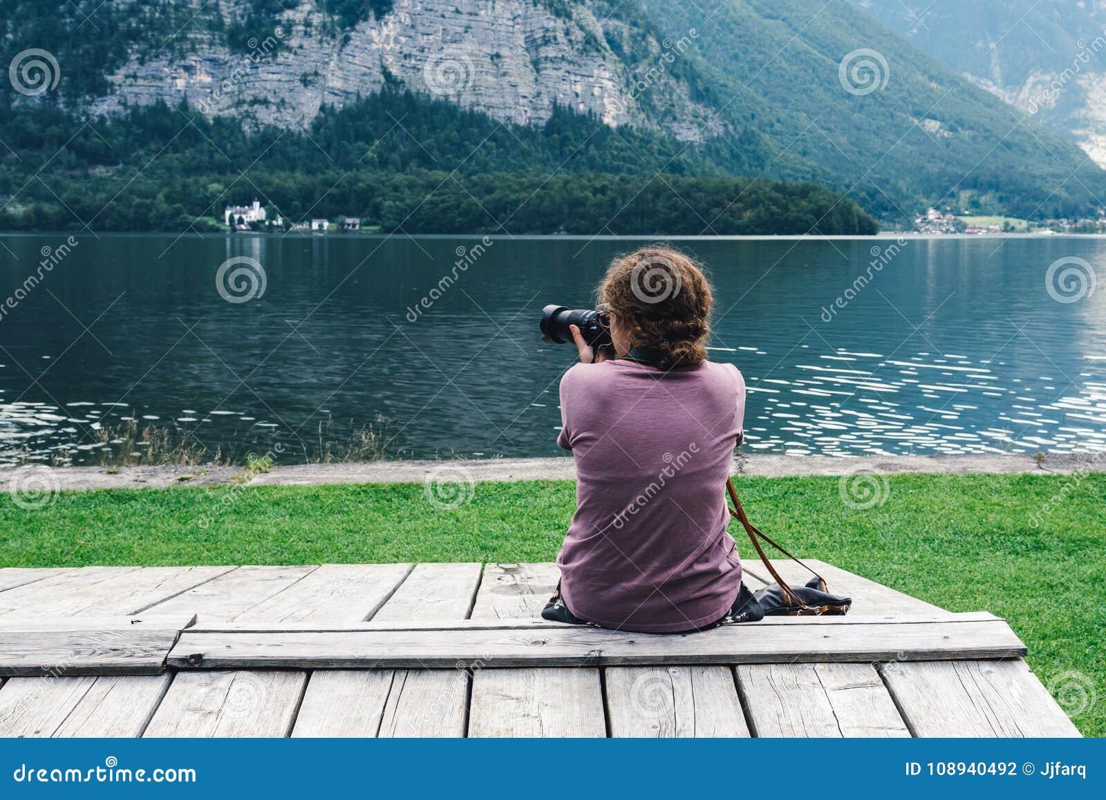 Vrouwenzitting terug op pijler bij oever van het meer