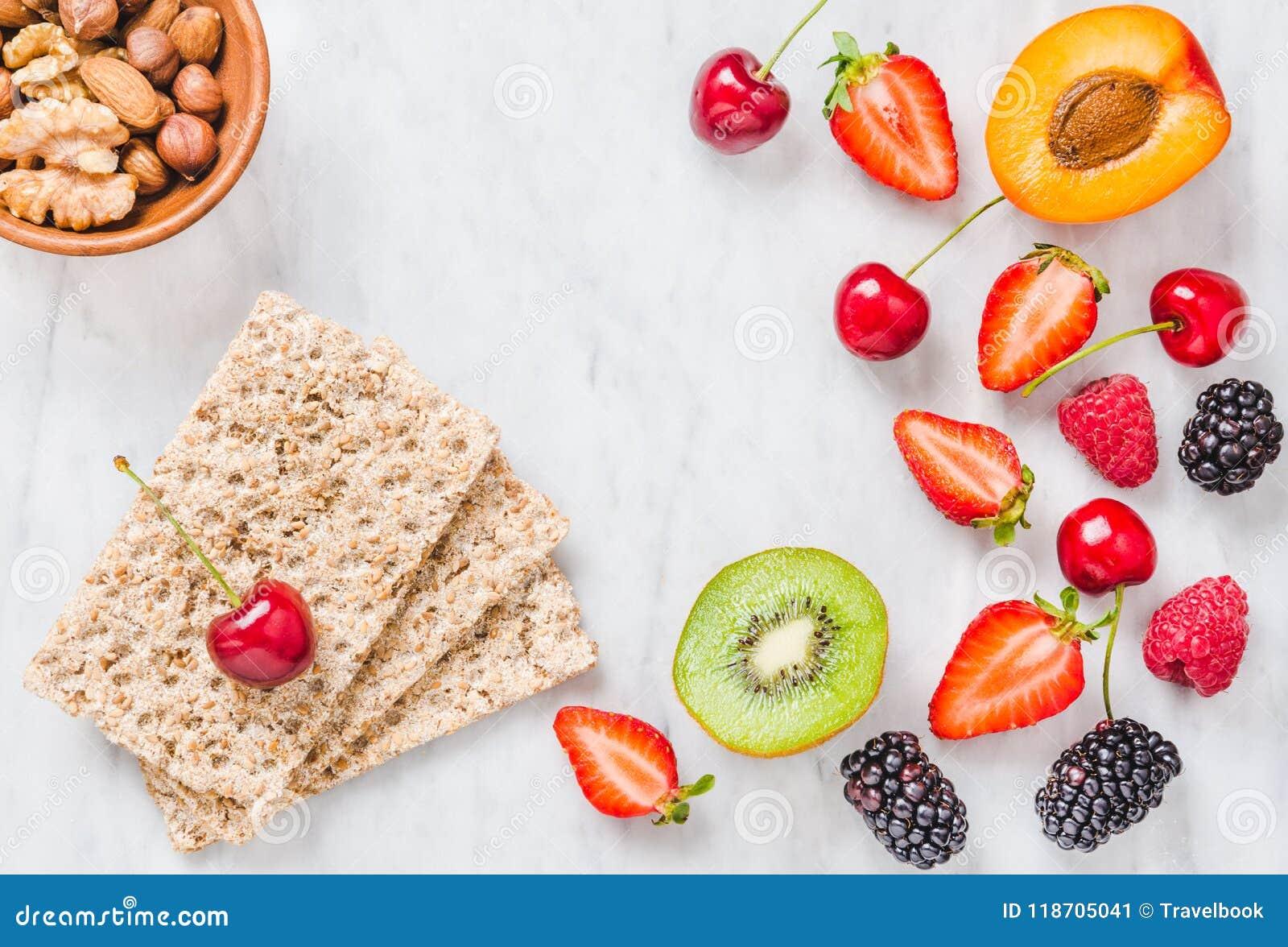 Vruchten, bessen en geheel korrel kernachtig brood op de witte marmeren ruimte van het lijstexemplaar Het concept het gezonde ete