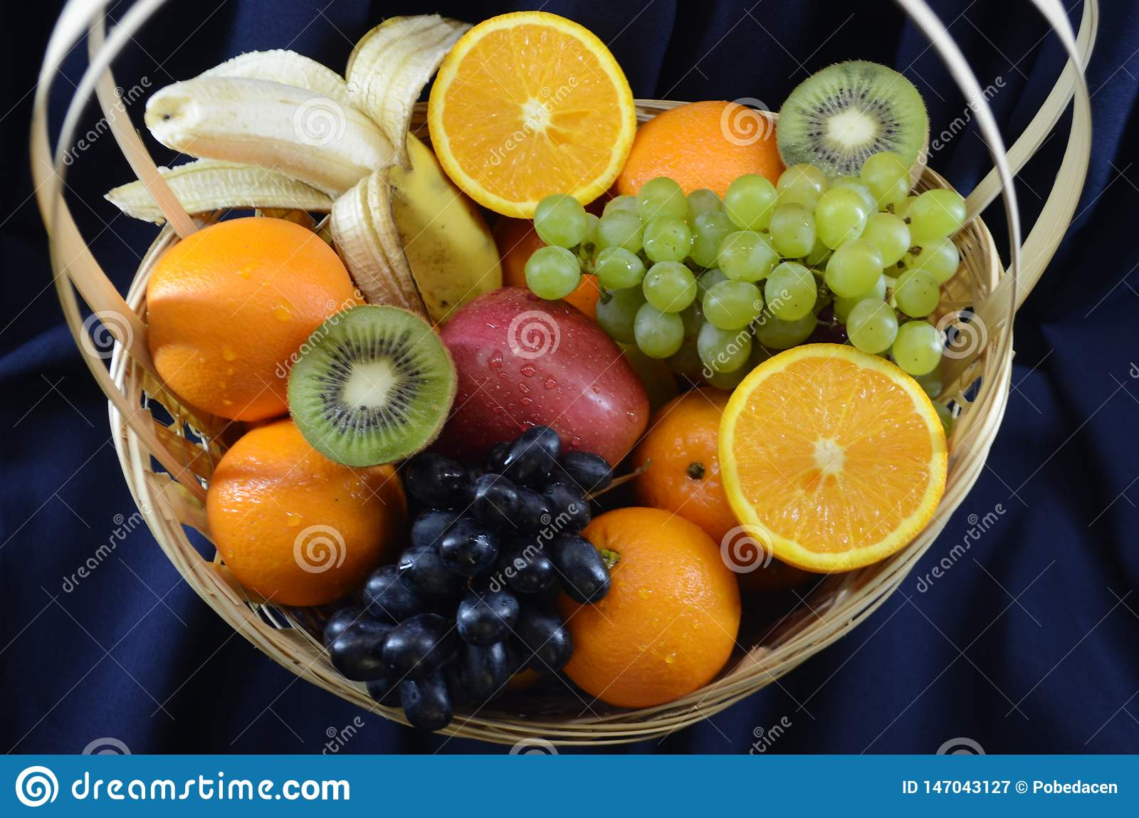 Vruchten in een rieten mand op een donkerblauwe stoffenachtergrond