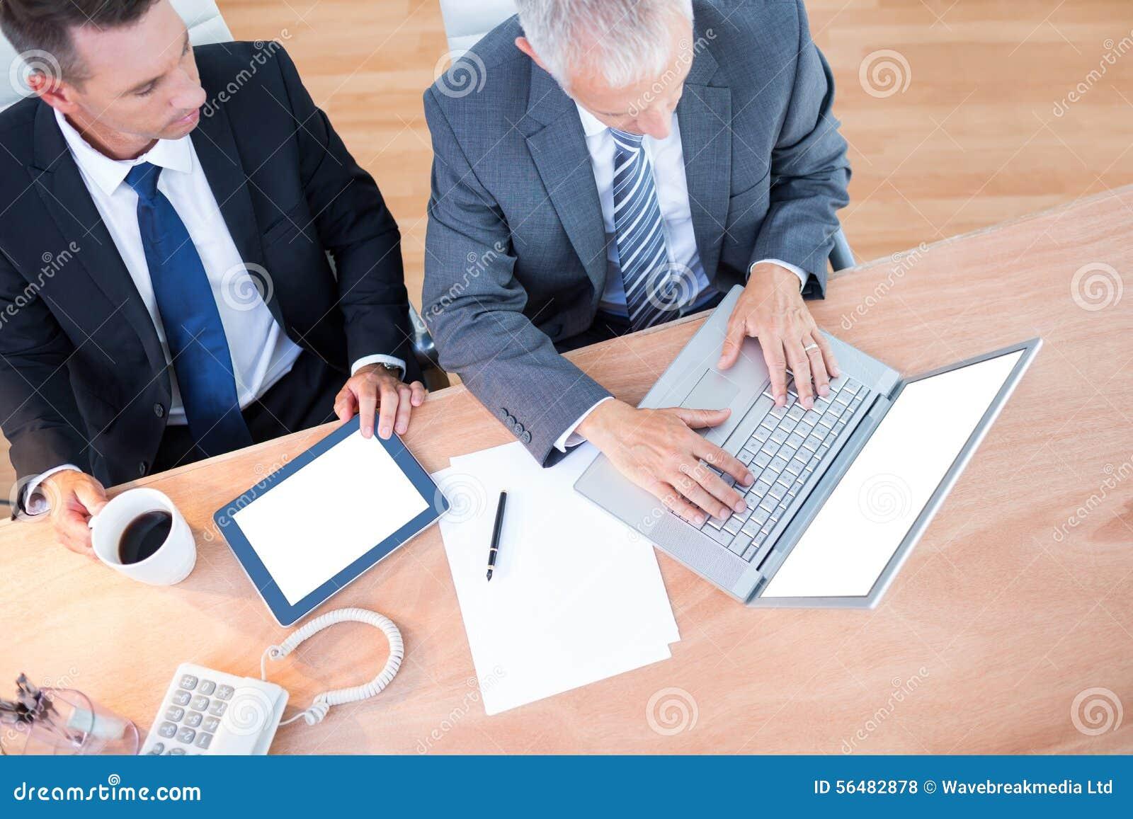 Vue élevée des hommes d affaires travaillant ensemble sur l ordinateur portable