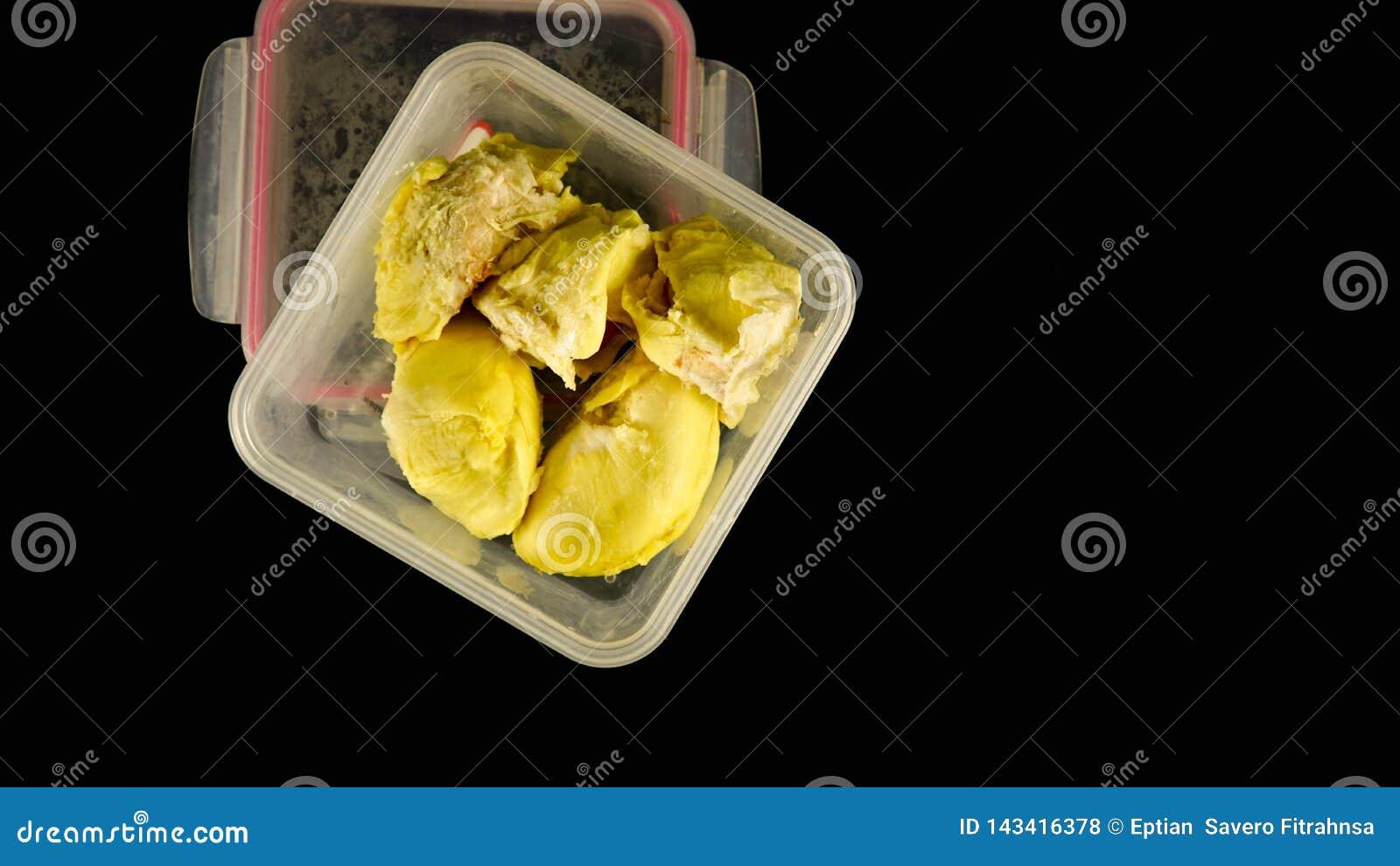 Vue étendue ou supérieure plate de fruit crémeux de durian à l intérieur de récipient en plastique dans le noir