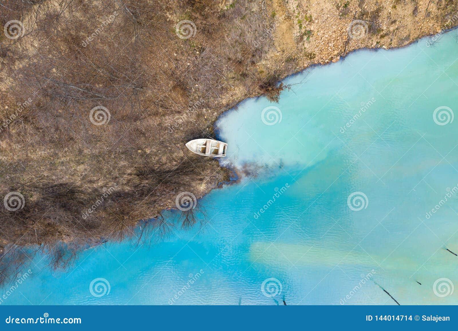 Vue aérienne d un bateau dans un lac de turquoise souillé avec du cyanure