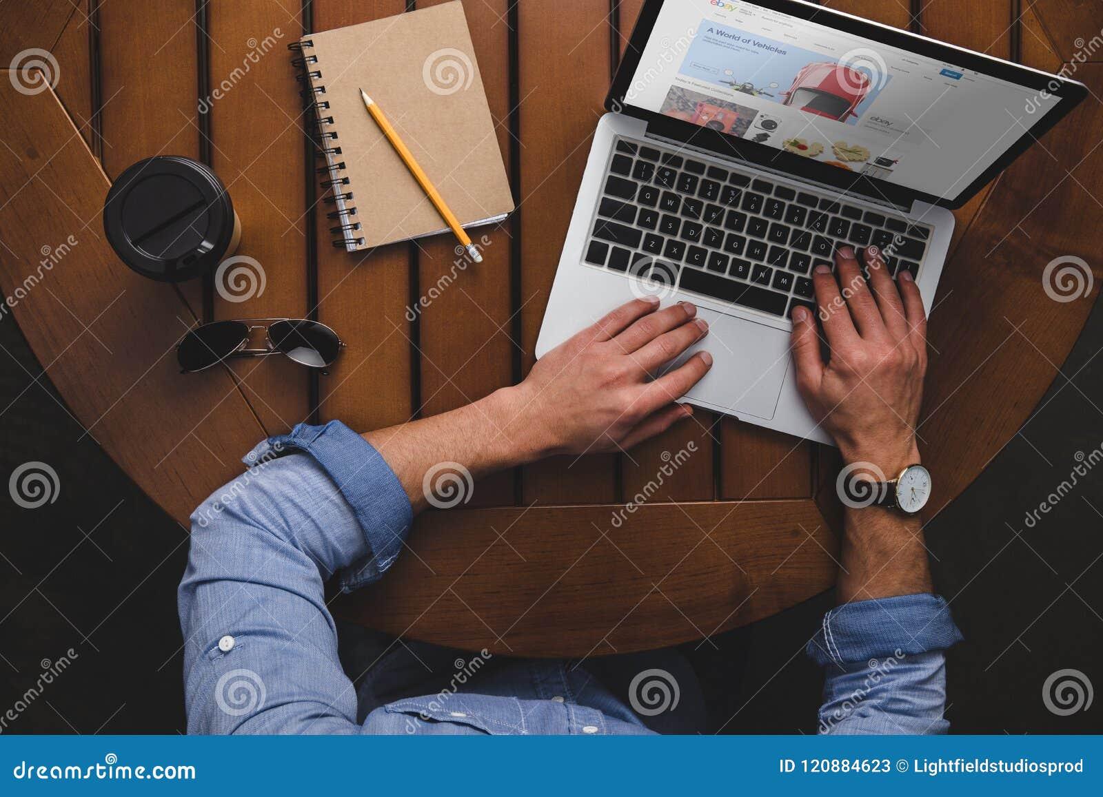 Vue aérienne de l homme à l aide de l ordinateur portable avec le site Web d ebay tout en se reposant à la table avec du café