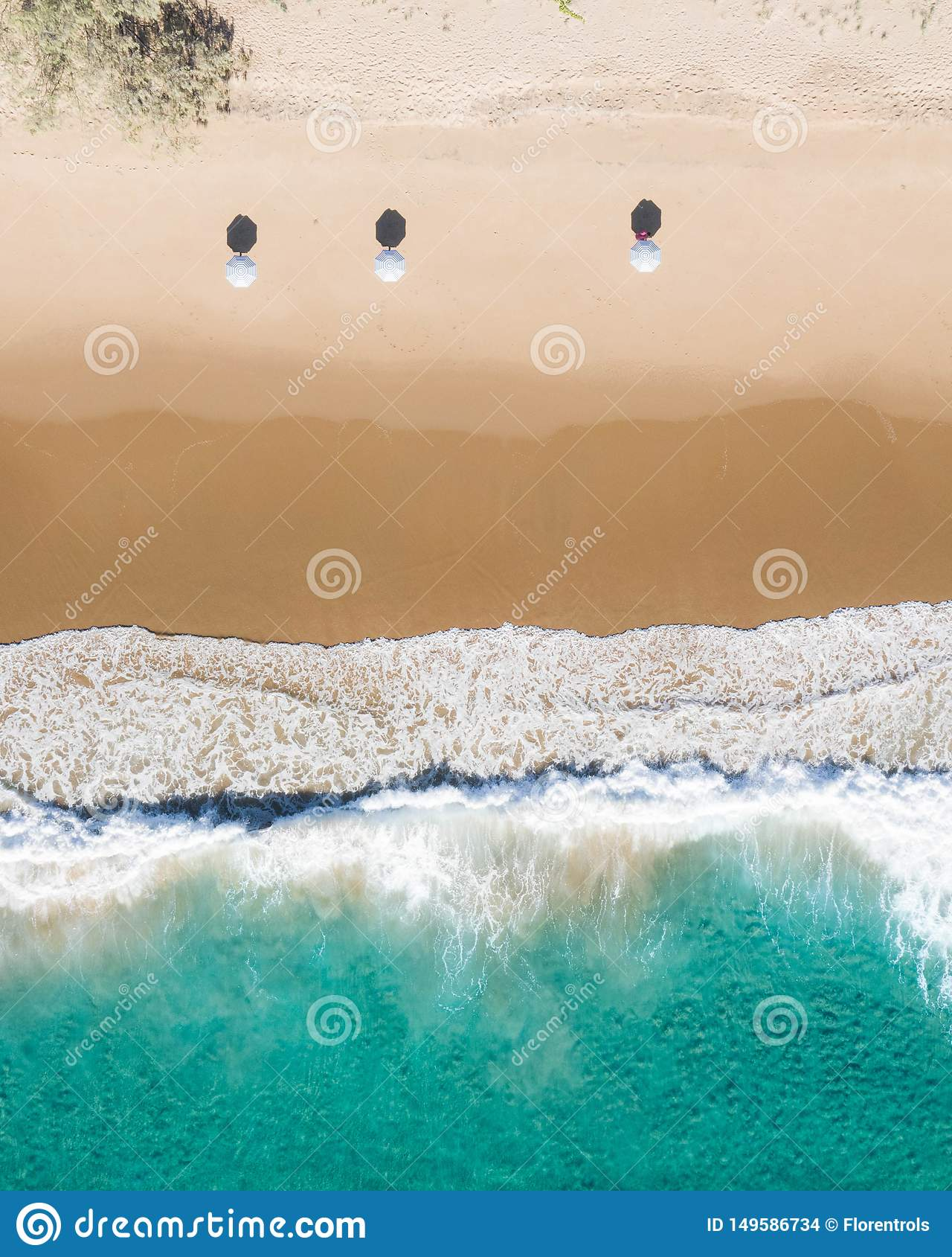 Vue aérienne de plage des parapluies, des vagues, de l océan de bleus et du vibraphone de détente