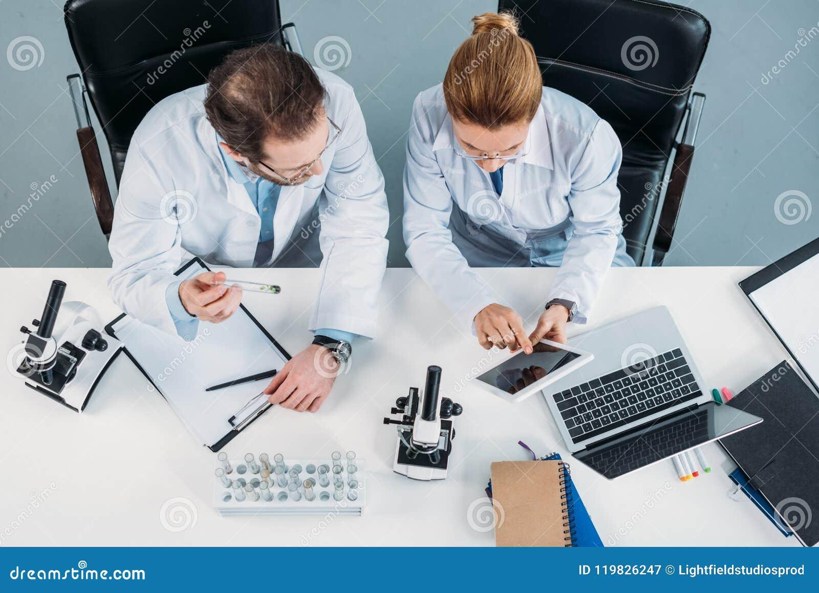 Vue aérienne des chercheurs scientifiques dans des manteaux blancs utilisant le comprimé ensemble sur le lieu de travail