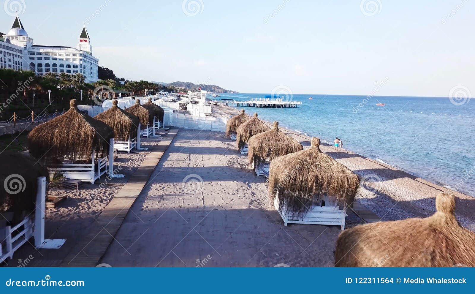 Vue aérienne des vagues, plage sablonneuse avec les parapluies tubulaires vidéo Vue supérieure de la plage sablonneuse avec des u