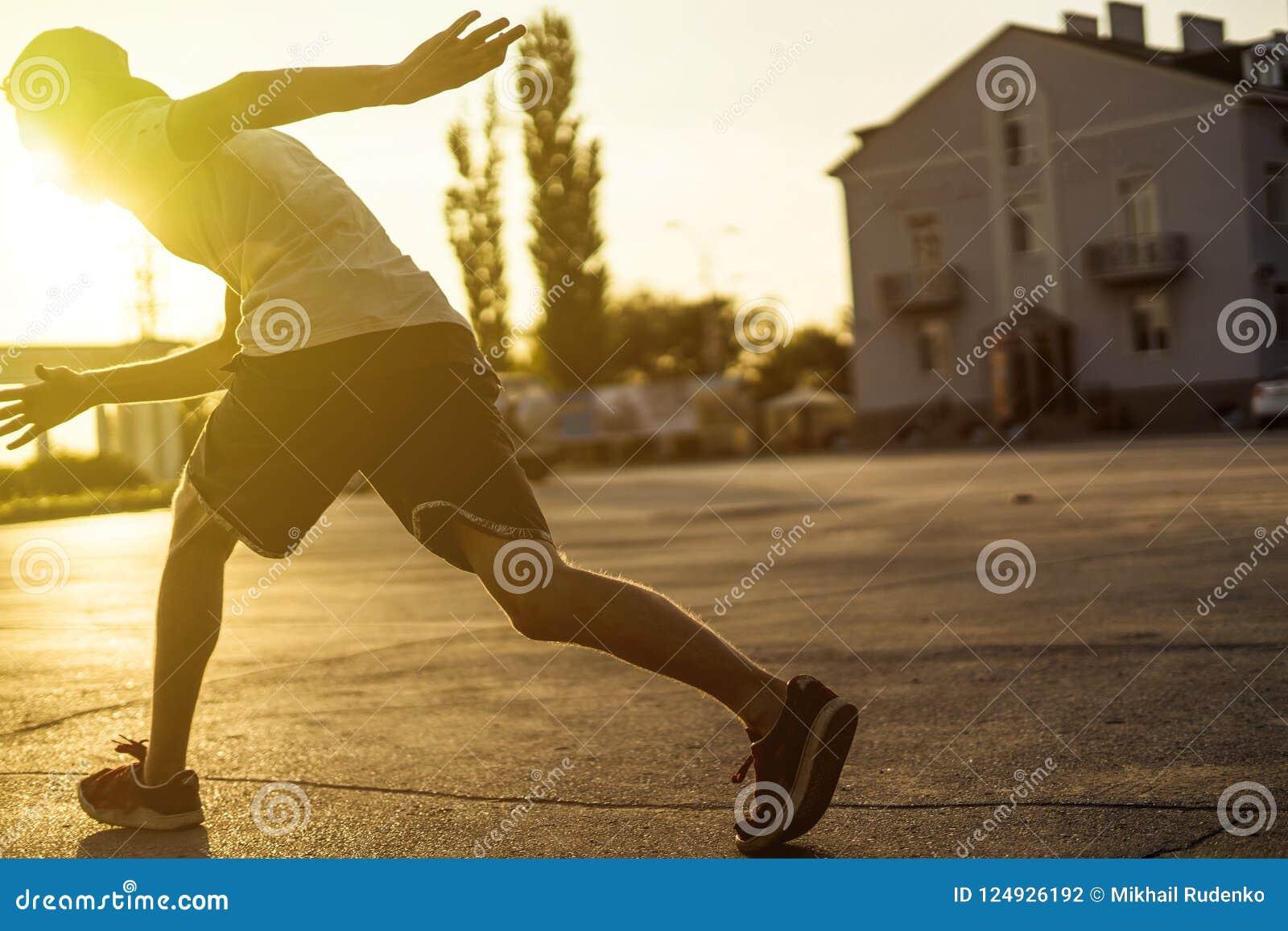 Vue arrière d athlète de jeune homme en silhouette occasionnelle fonctionnant dans la ville urbaine sur un coucher du soleil