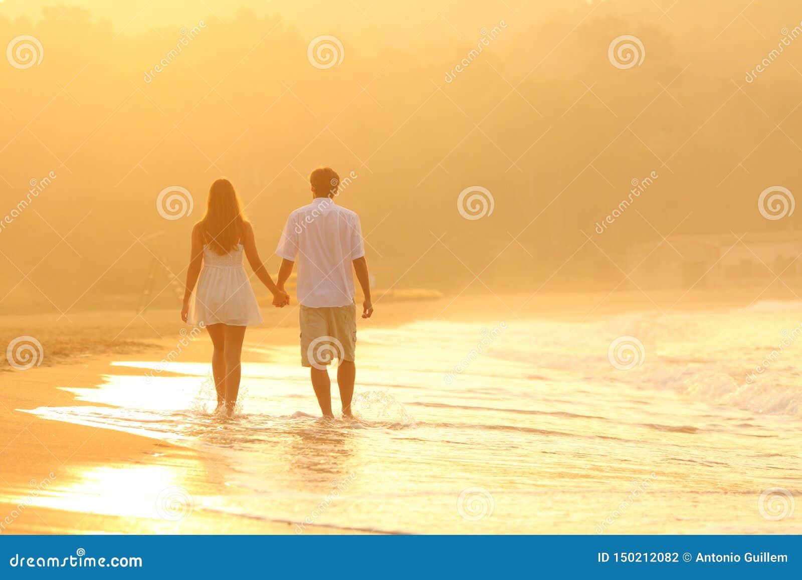 Vue arrière d un couple au coucher du soleil marchant sur la plage