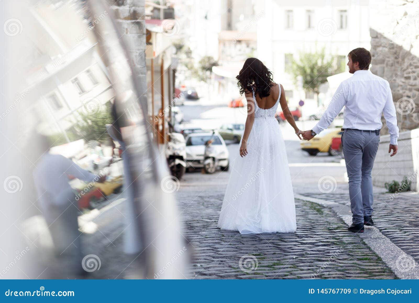 Vue arrière d un couple romantique de promenades de nouveaux mariés sur la vieille rue Grèce Mariage en Gr?ce