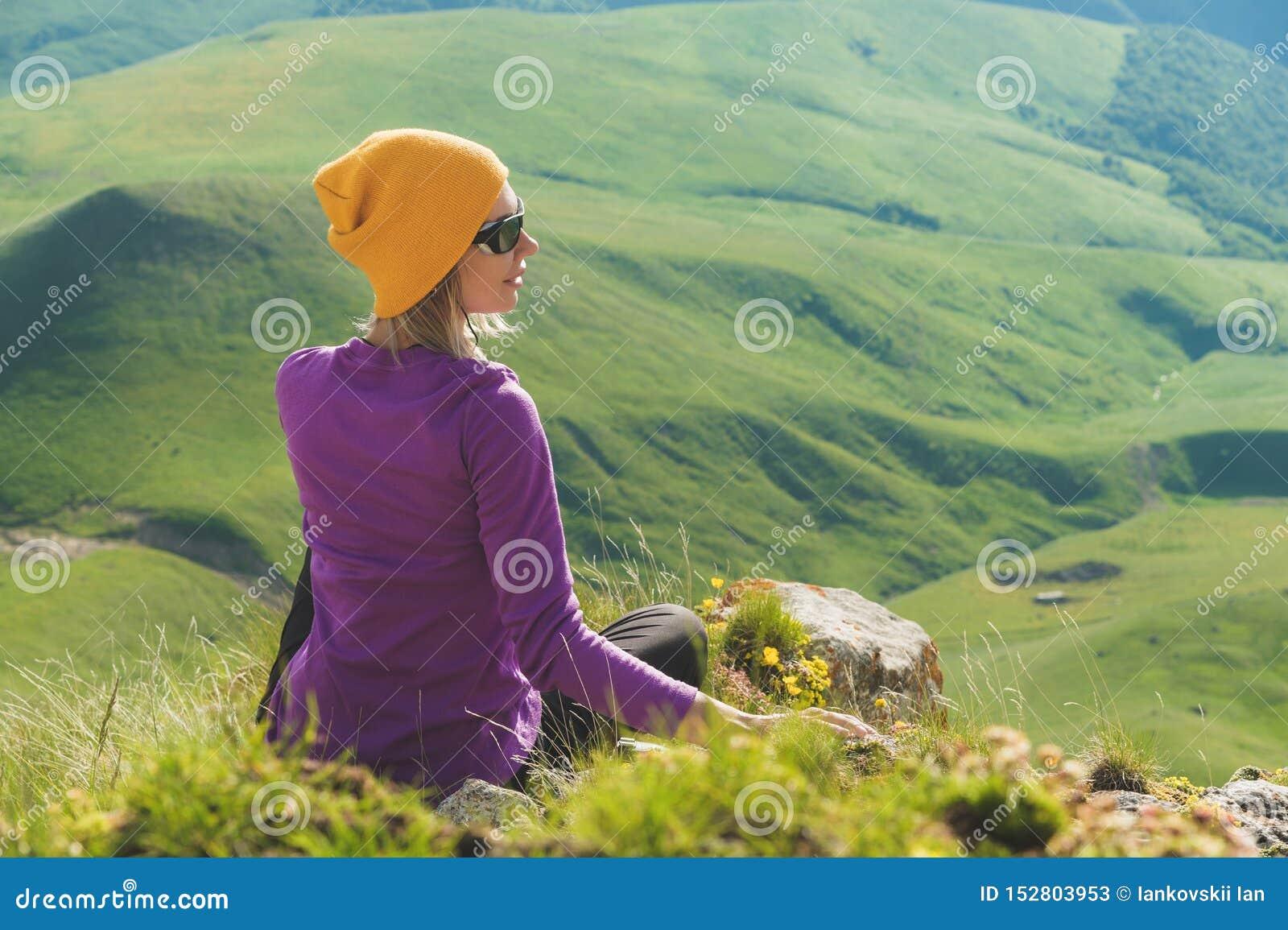 Vue arrière d un touriste féminin attirant s asseyant sur les lunettes de soleil de port d une colline herbeuse Appréciant un jou