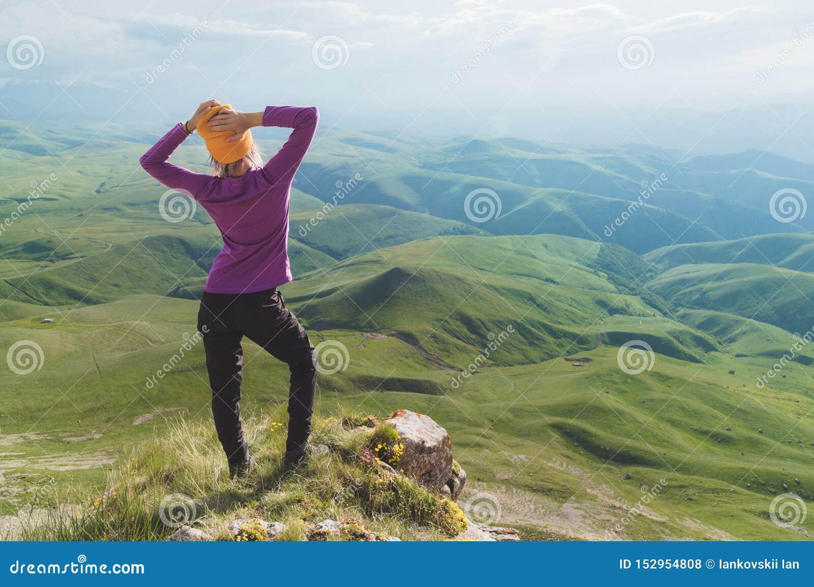 Vue arrière d une position de touristes femelle attrayante sur les lunettes de soleil de port d une colline herbeuse Appréciant u