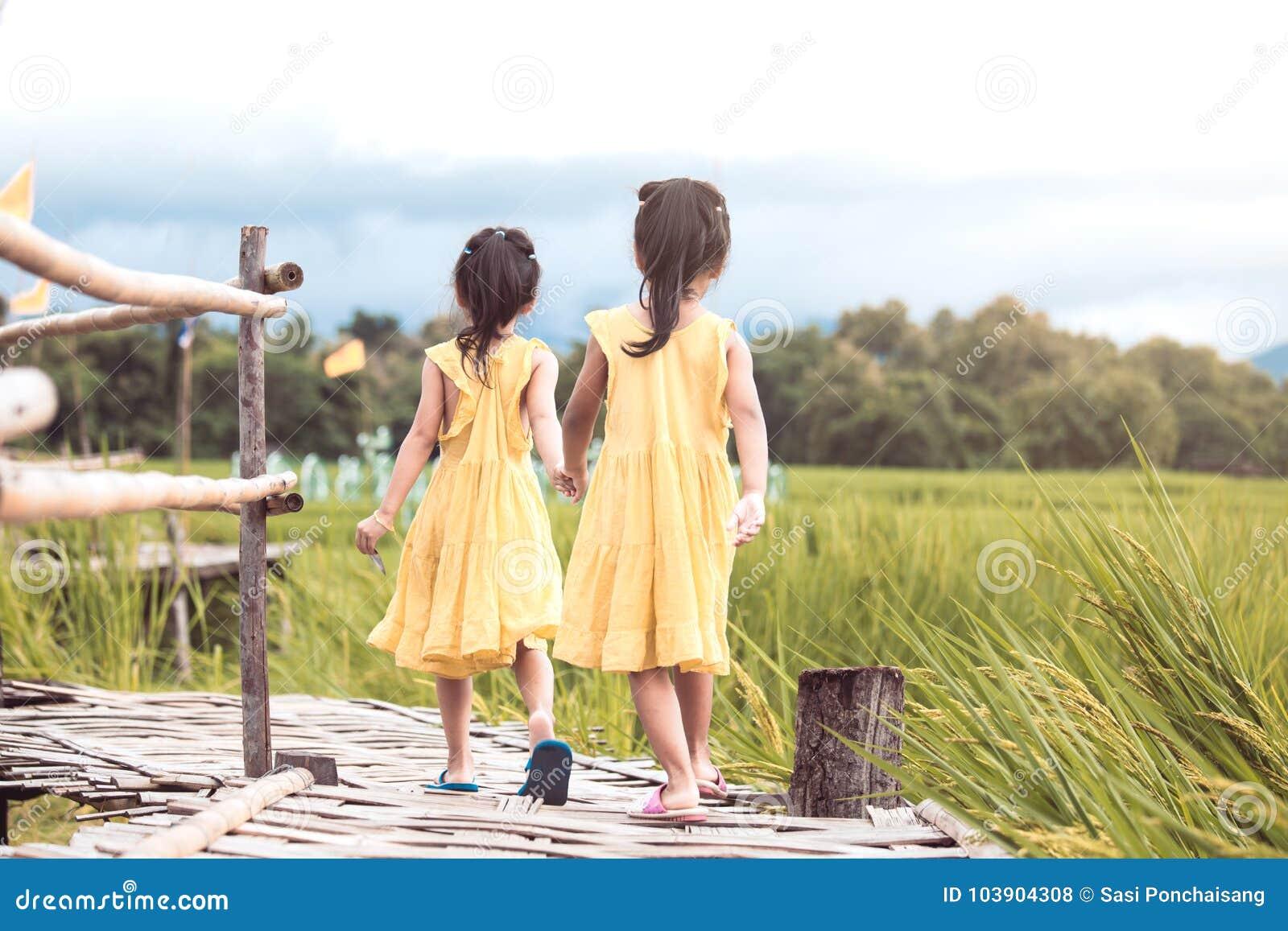Vue arrière de deux petites filles tenant la main et marchant ensemble