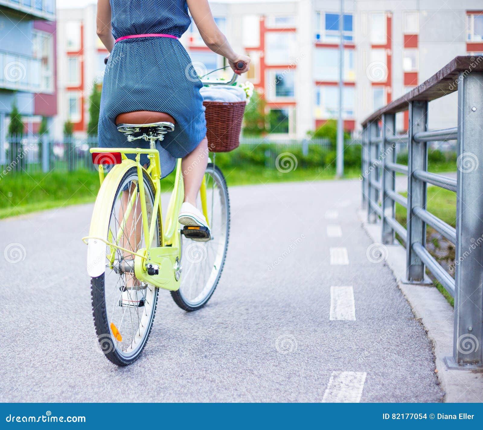 Vue arrière de femme dans le vélo de vintage d équitation de robe avec le panier