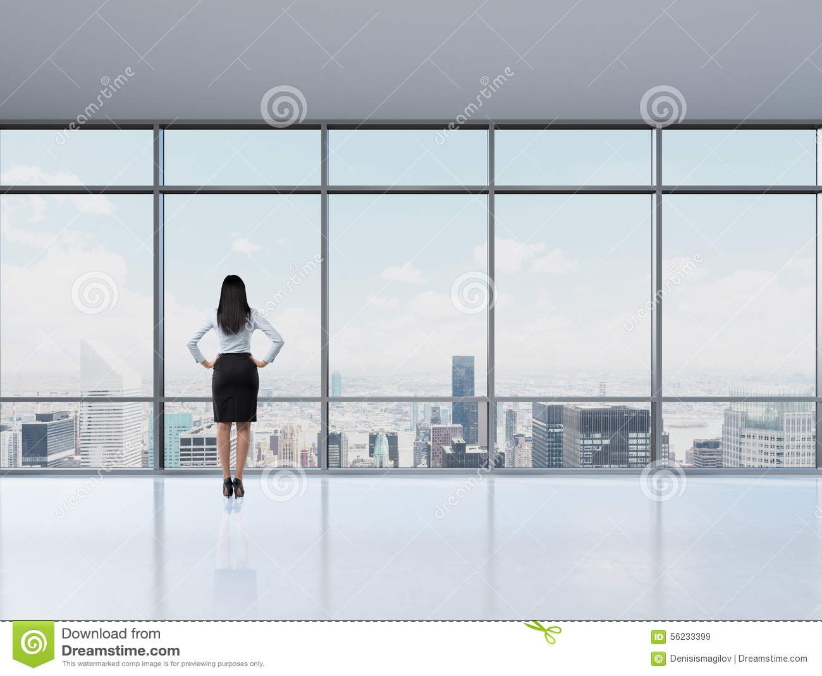 Vue arrière de femme de brune dans le bureau qui regarde par la fenêtre
