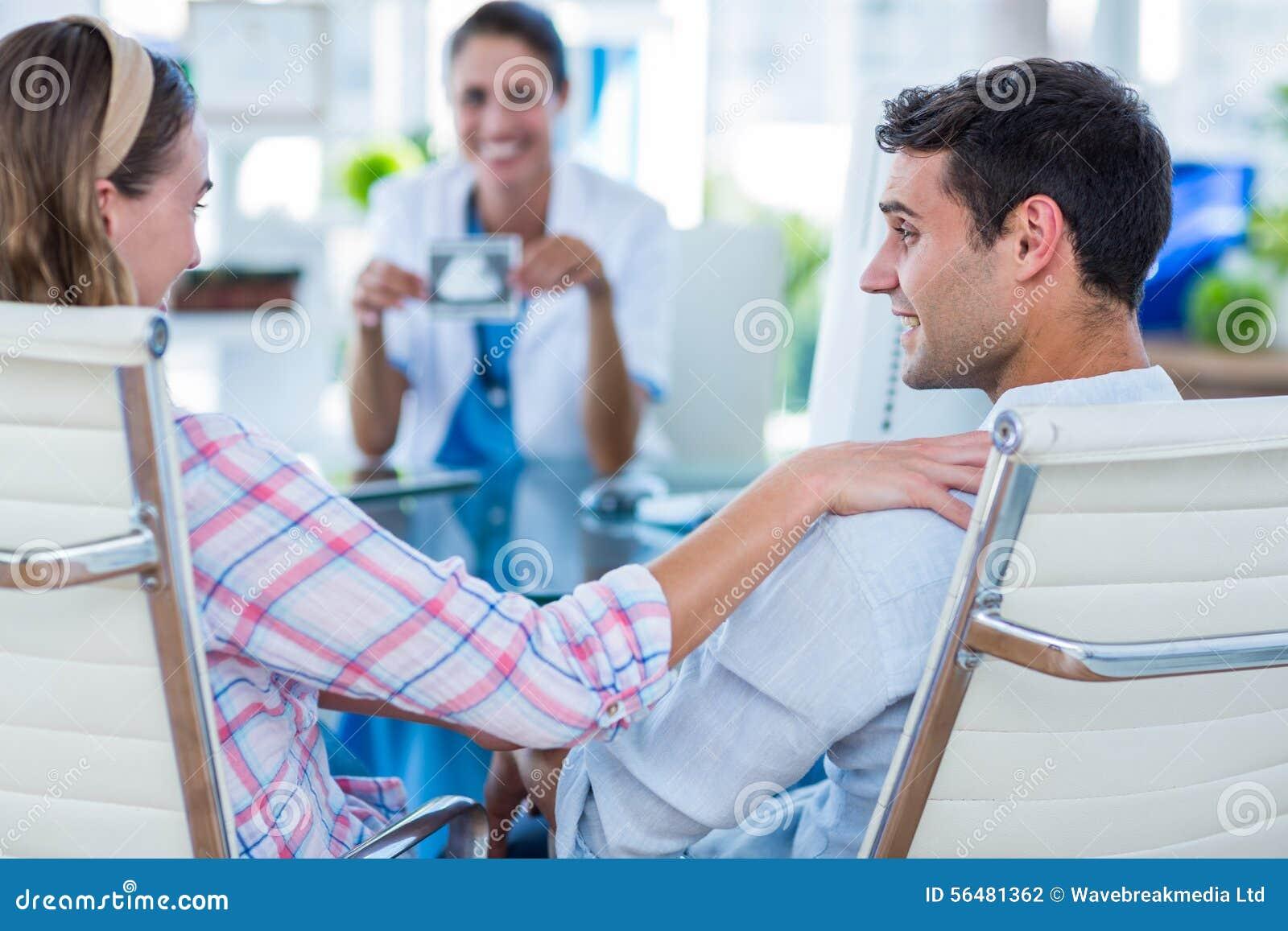 Vue arrière de femme enceinte et son de mari discutant avec le docteur