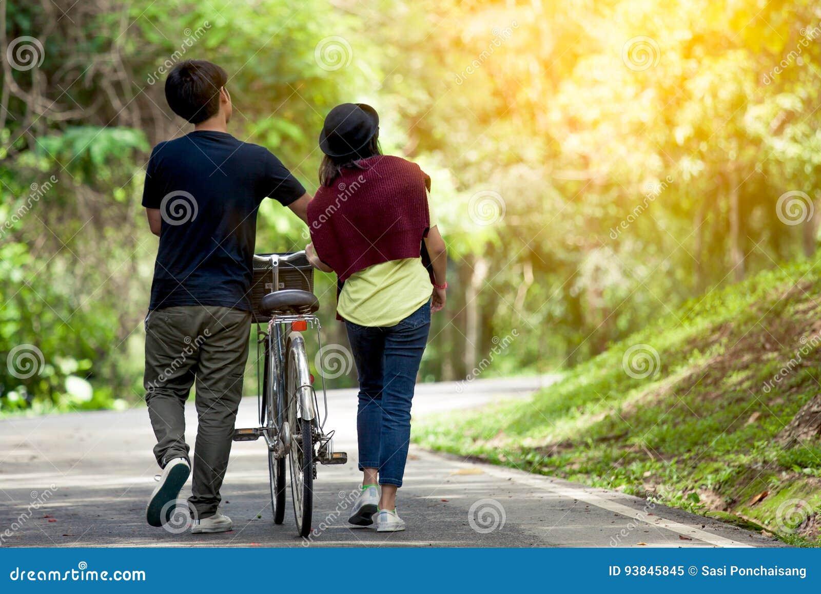 Vue arrière de jeunes couples marchant ainsi que la bicyclette