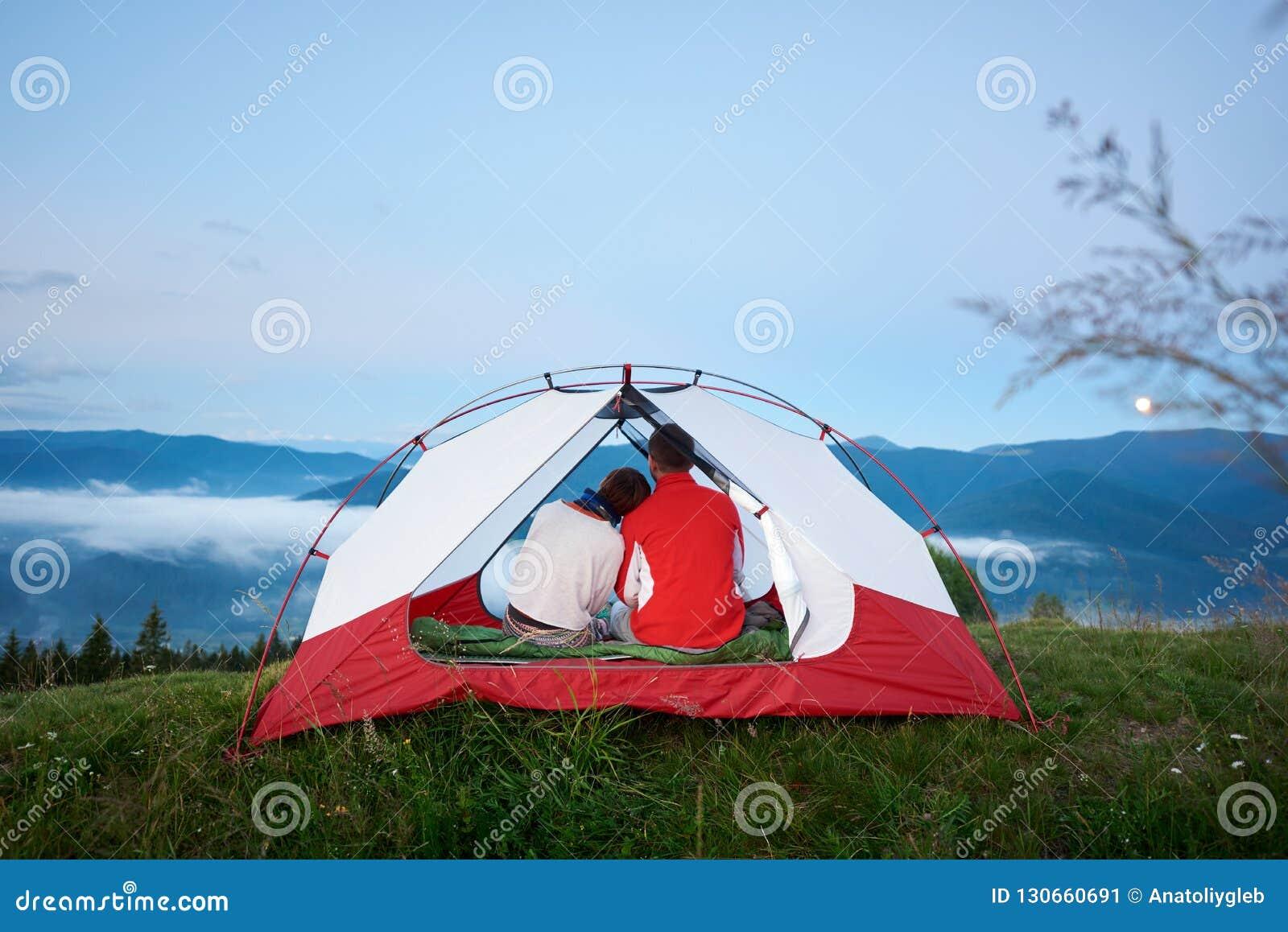 Vue arrière de jeunes couples se reposant dans la tente regardant des montagnes