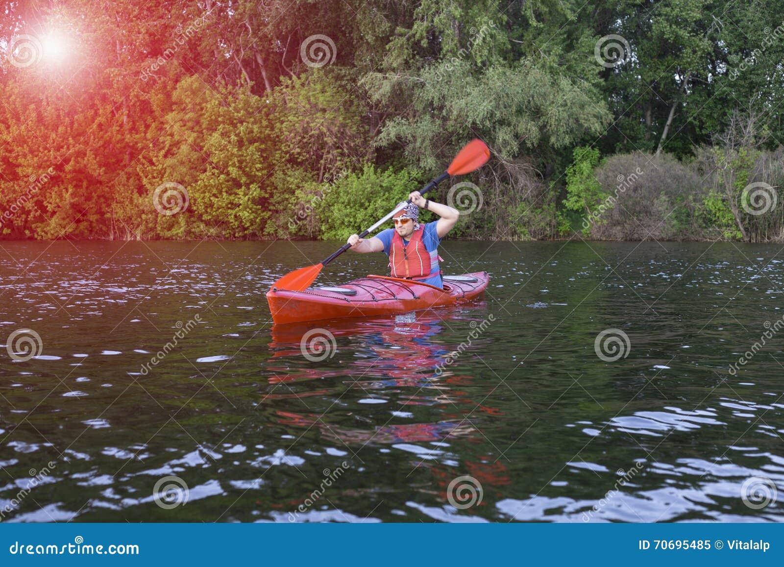 Vue arrière de l homme barbotant le kayak dans le lac avec la femme à l arrière-plan Couplez kayaking dans le lac un jour ensolei