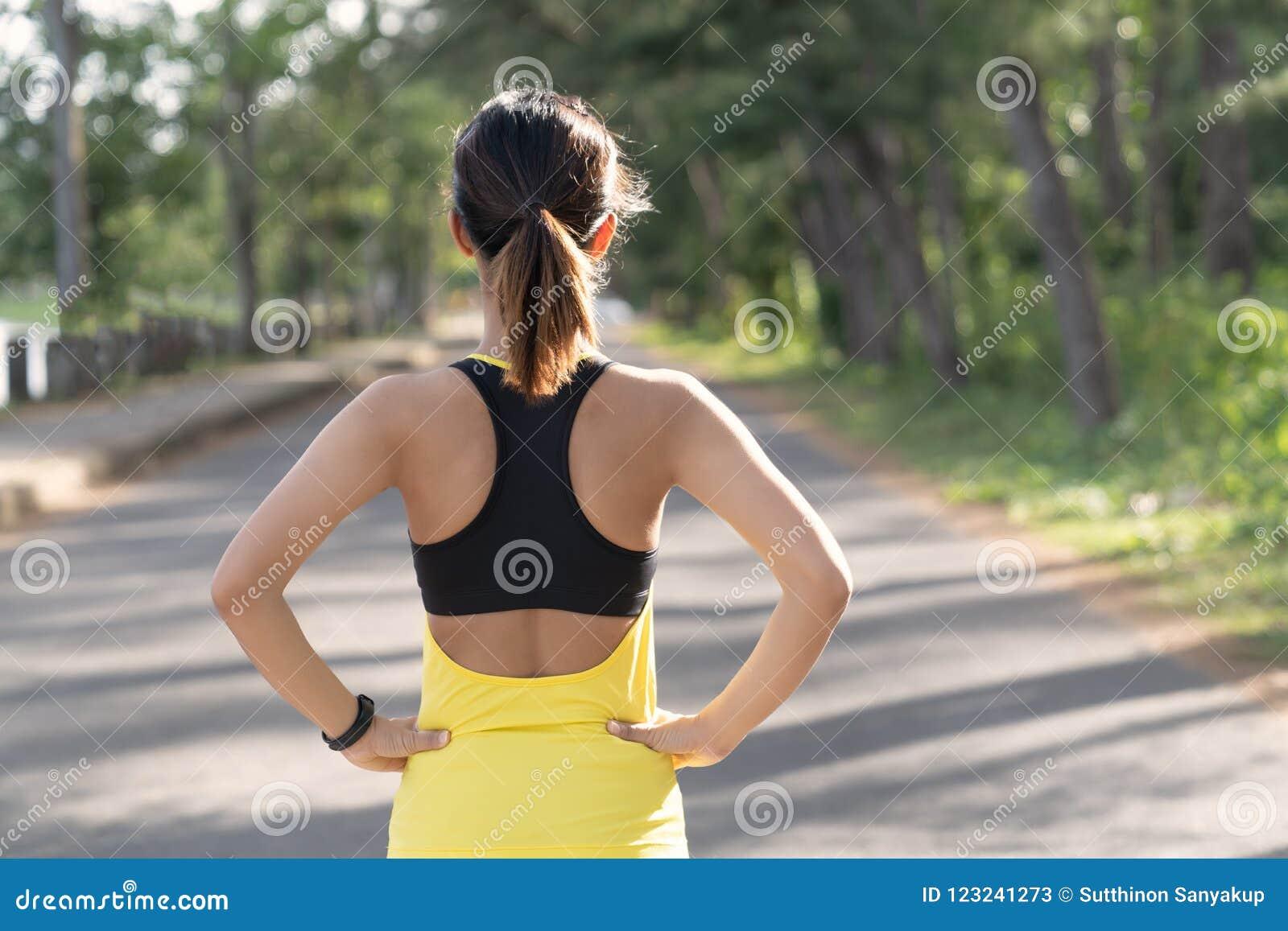 Vue arrière de la jeune femme de forme physique courant sur la route le matin, les personnes et le concept de sport, foyer sélect